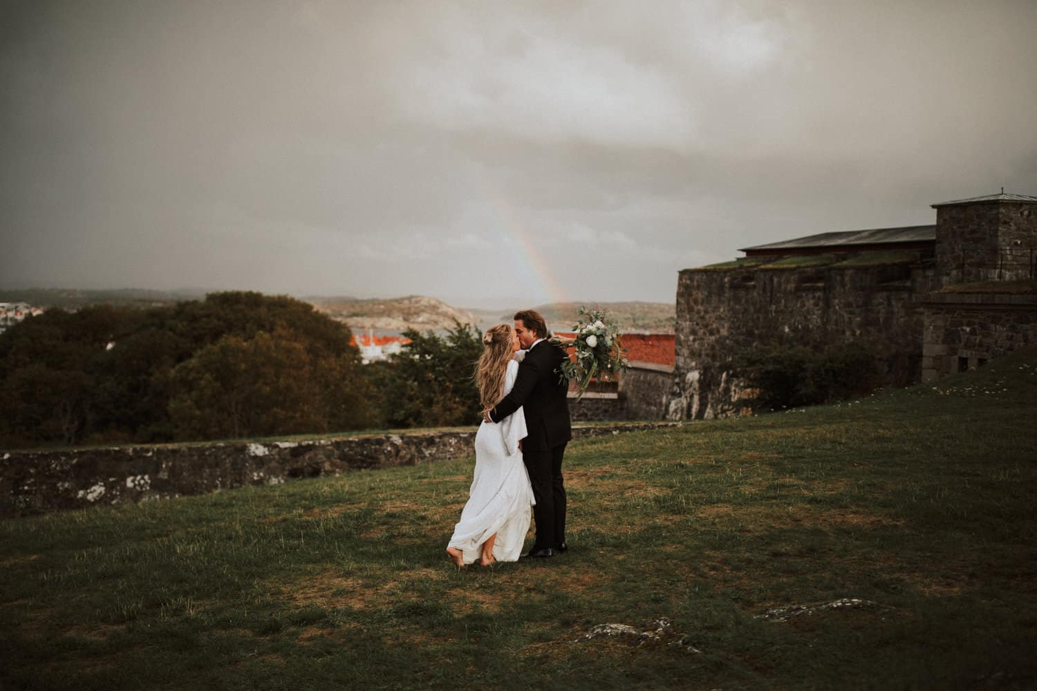 A wedding couple is standing on a meadow and kissing each other.