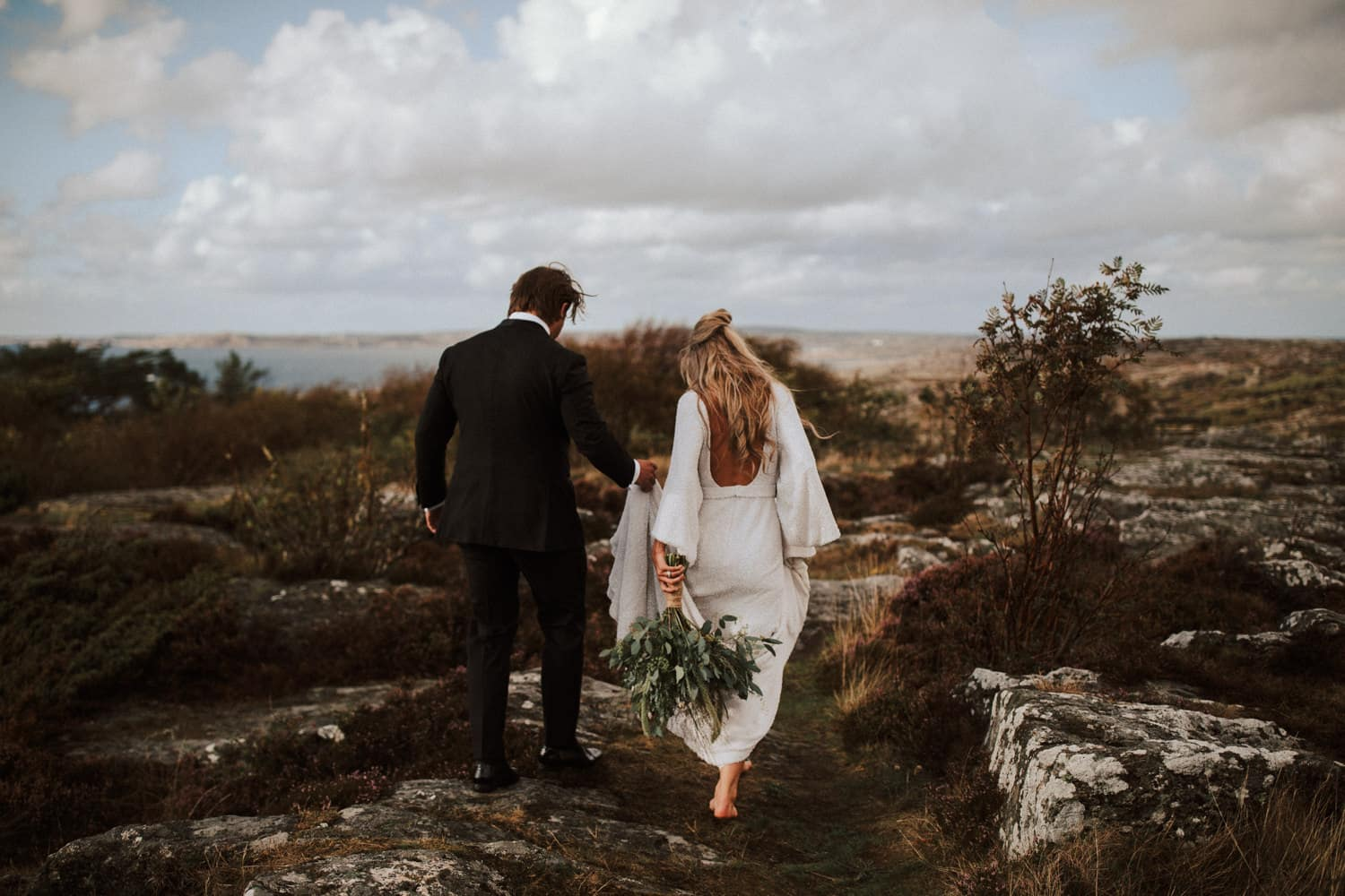 A wedding couple is walking through a rocky path and a meadow.