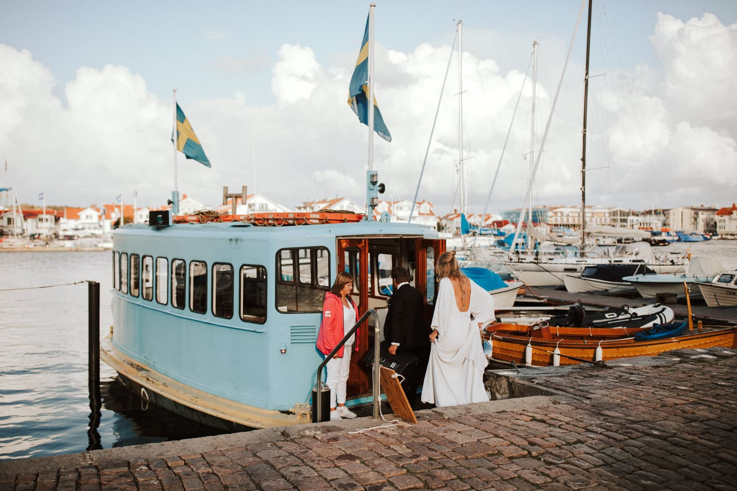 A wedding couple is walking into a blue boat.