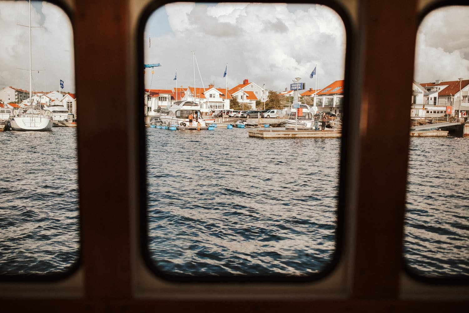 The view out of a boat window shows the ocean, other boats and buildings.
