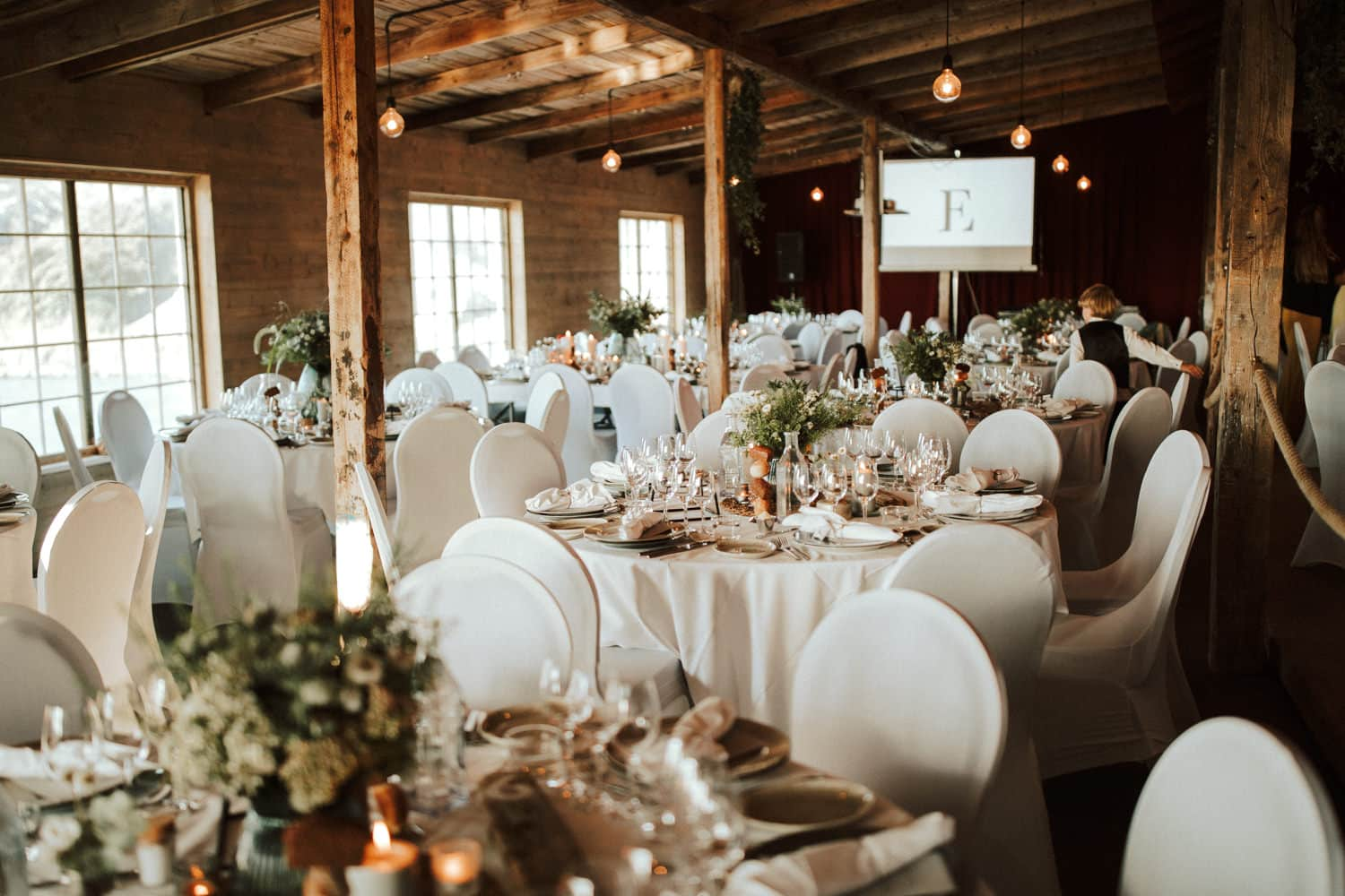 The location features white wedding tables and white chairs.