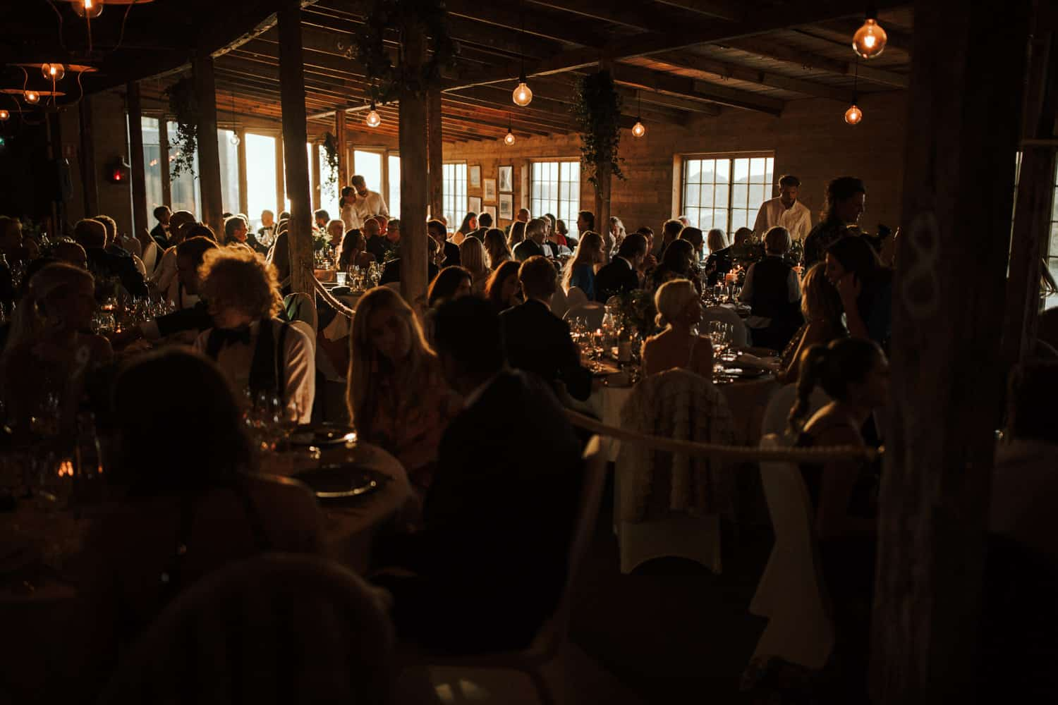 Wedding guests are sitting at tables in a rustic room.