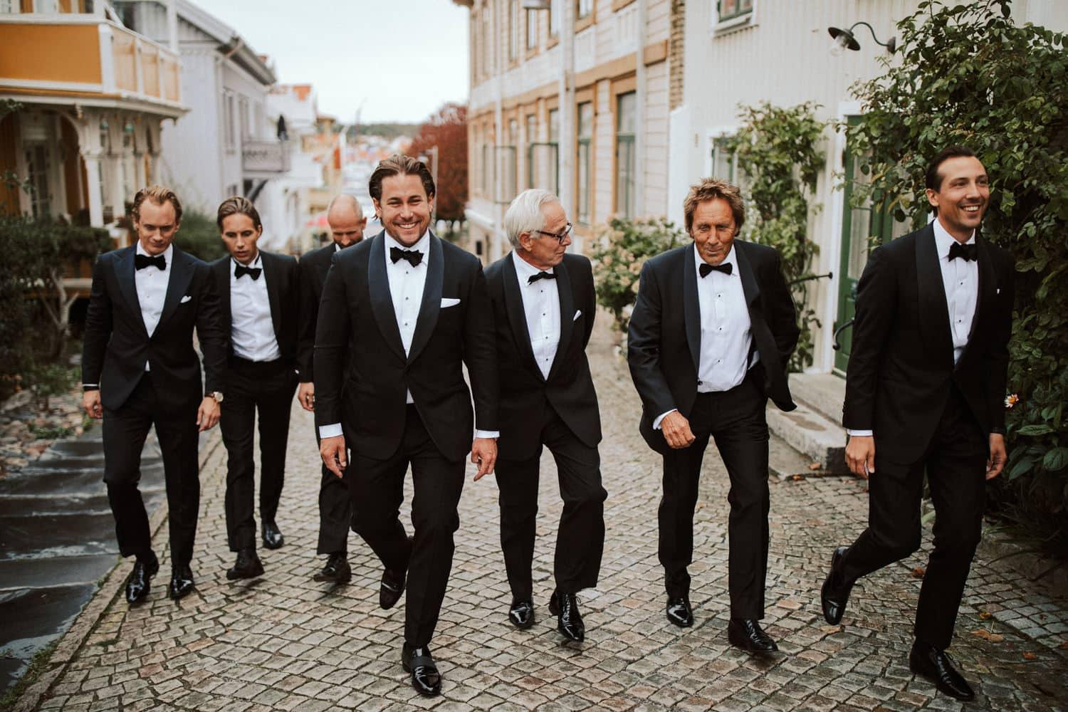The groom and his groomsmen are walking towards the wedding location.