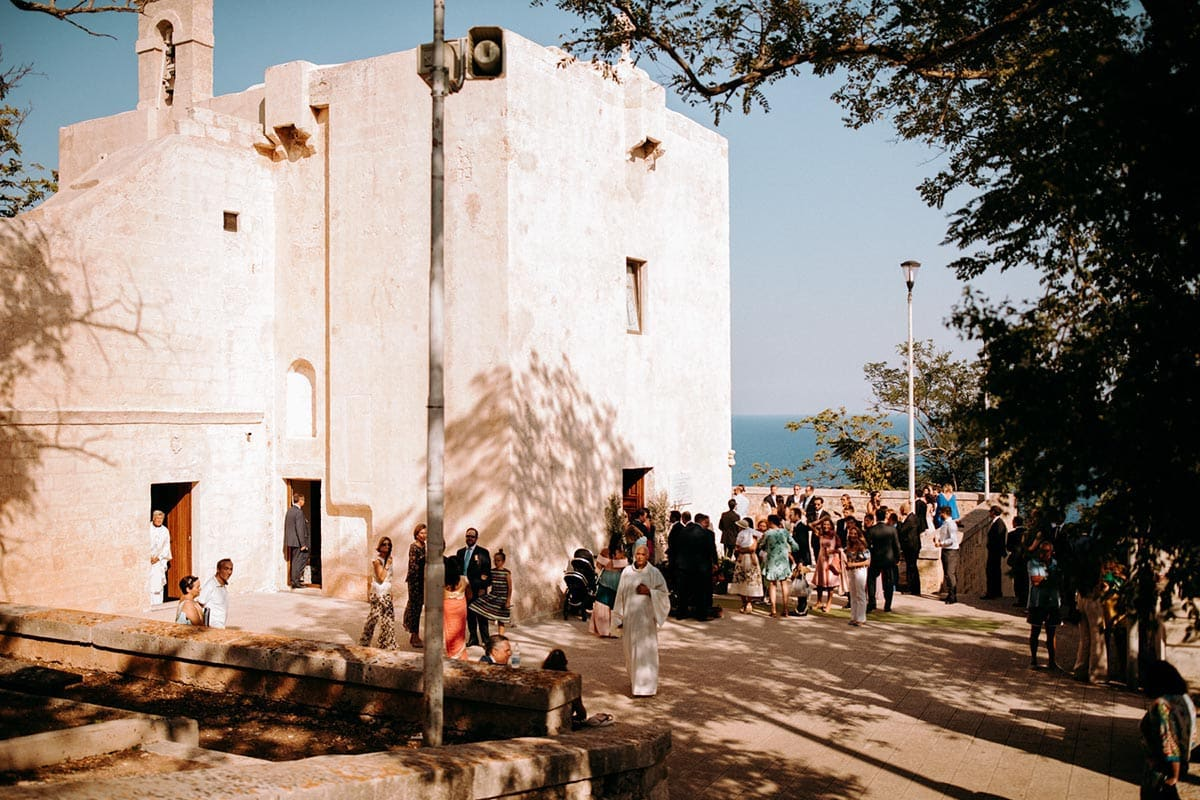 This Italy wedding photo shows a small church and wedding guests next to the venue.
