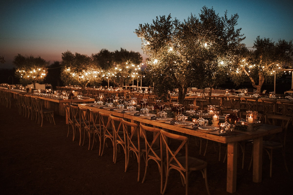 The wedding location features decorated tables and light bulb garlands, hanging in the trees.