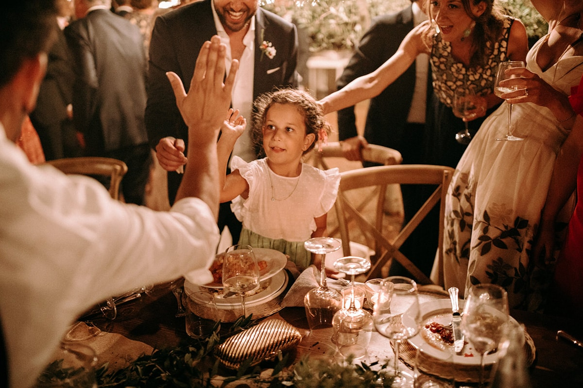 A little girl is high giving a wedding guest.