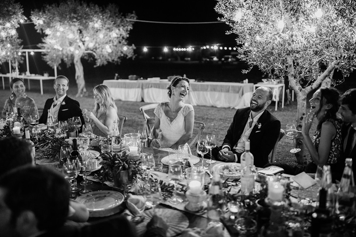 The wedding couple and their guests are laughing.