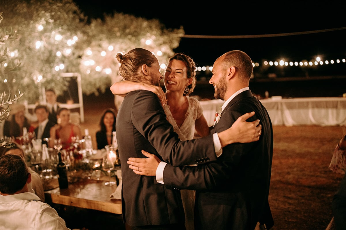 The wedding couple is hugging a groomsman.