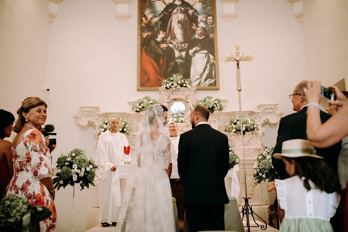 The bride and the groom are standing in front of the altar.