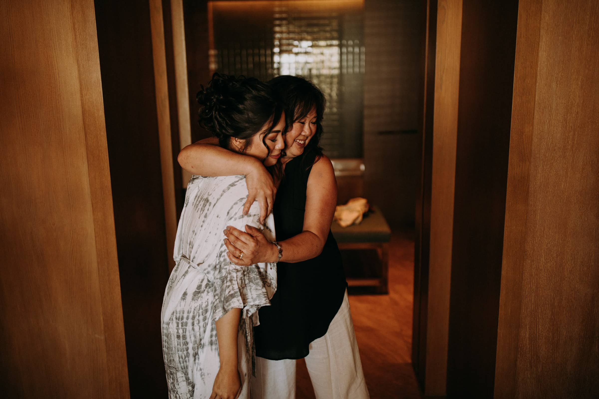 A bride and mother hug before the wedding.