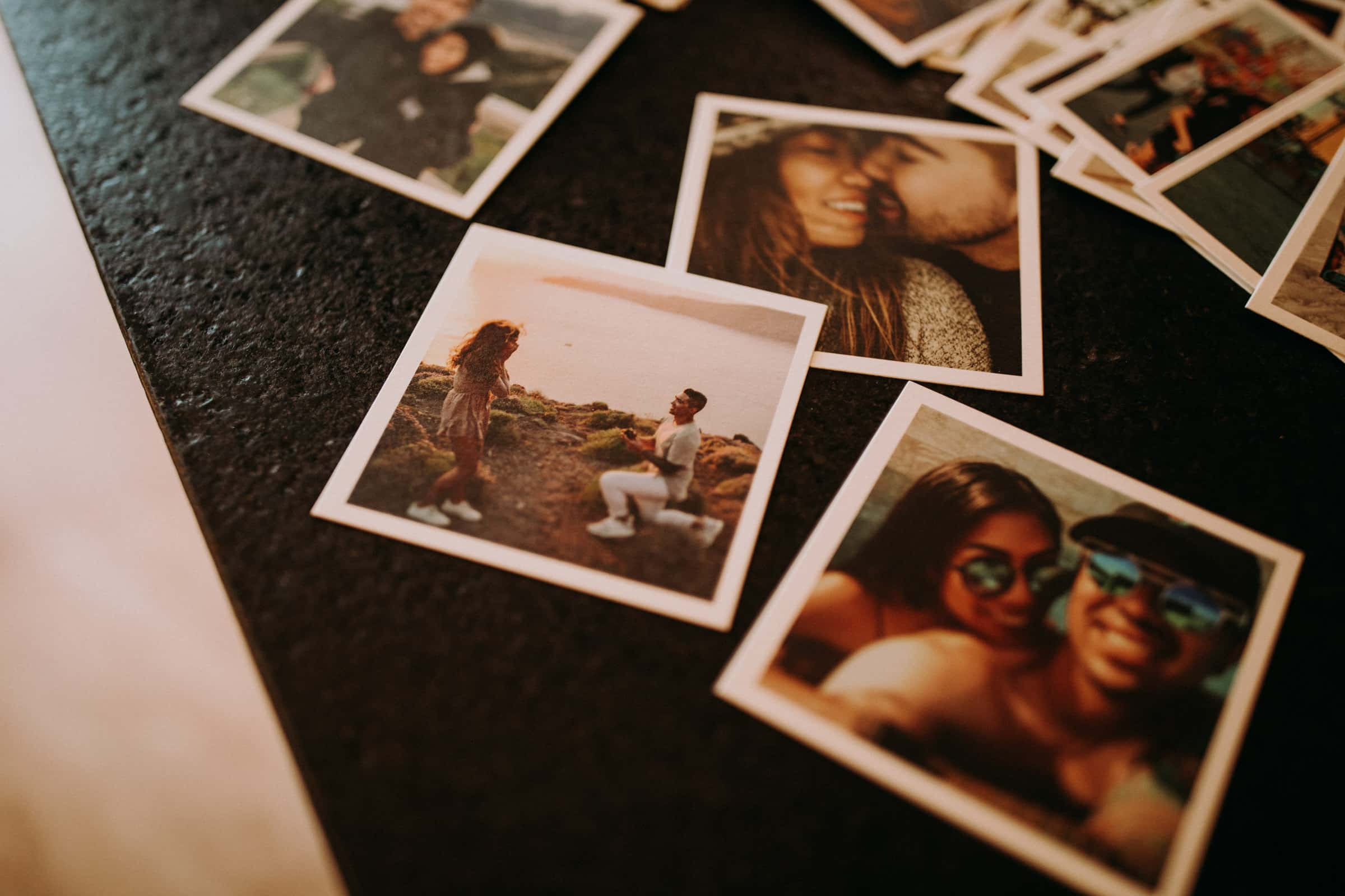 Engagement photos are spread out on a table.
