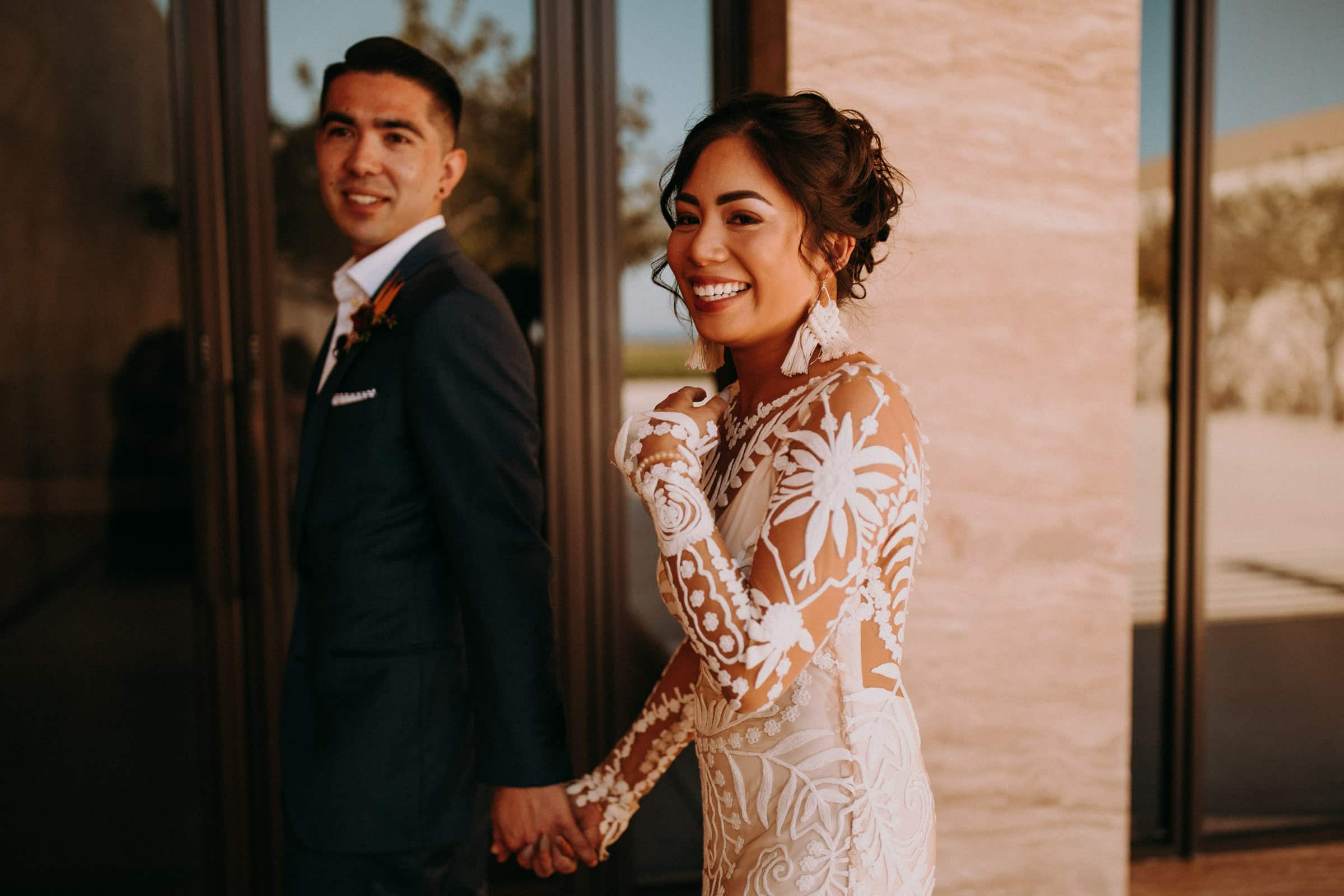 A wedding couple is holding hands and smiling.