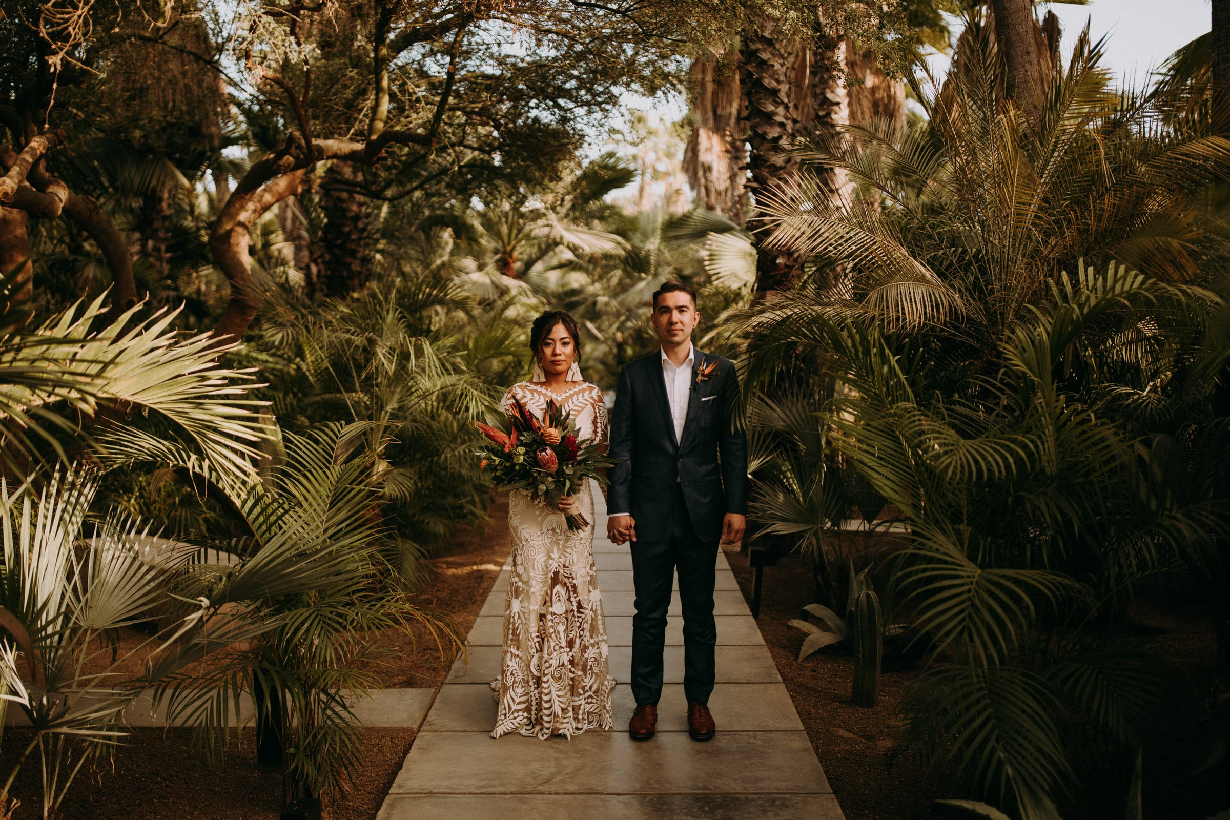 Acre Baja Wedding couple is standing on a path and holding hands.