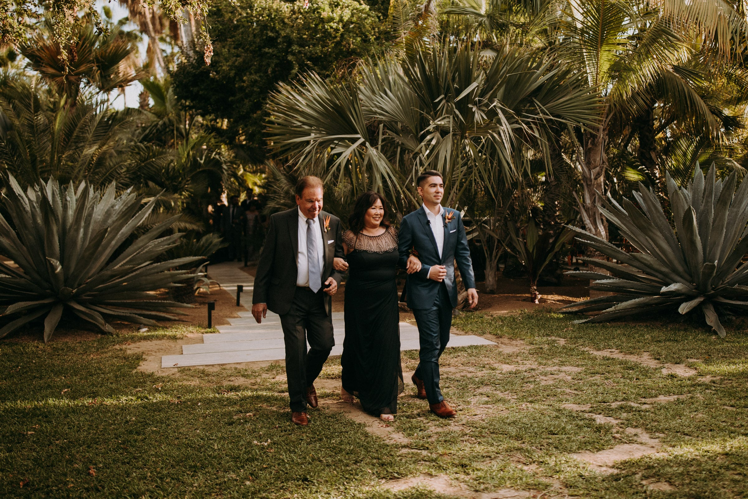 A groom is walking down the aisle with his parents at the San Jose Del Cabo Wedding.