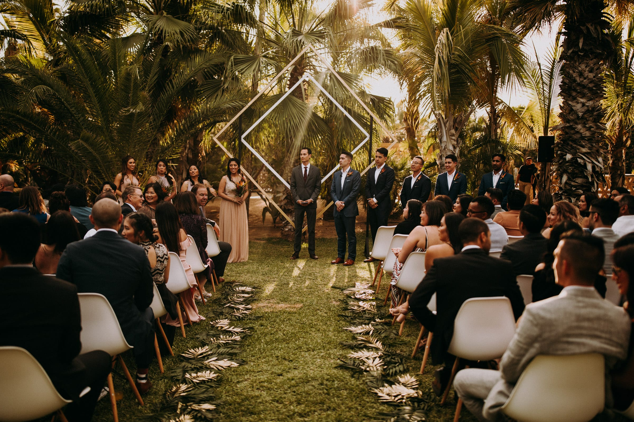 A groom is standing at the end of an aisle with his wedding guests next to him at the San Jose Del Cabo Wedding.