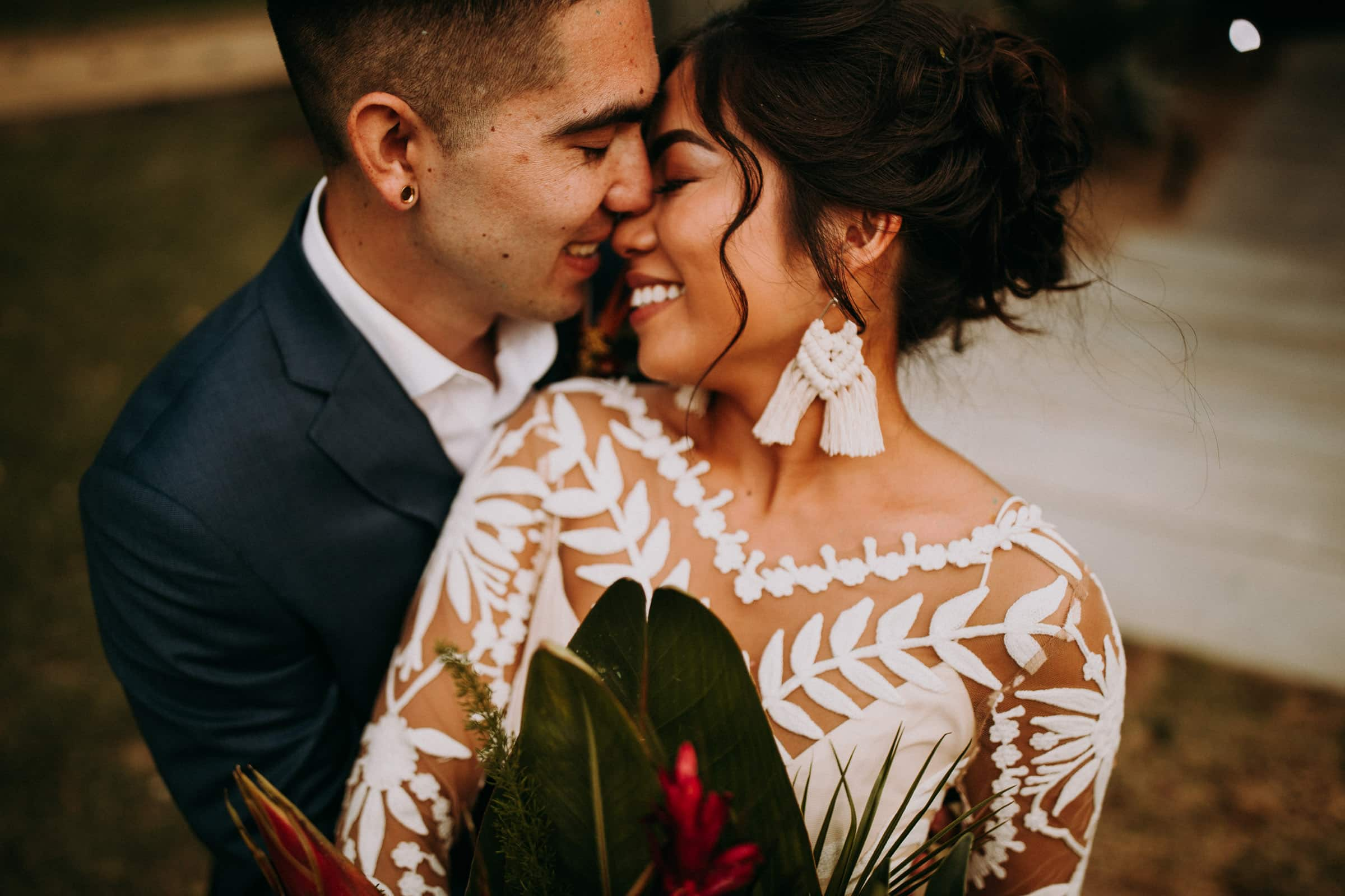 A closeup shows a wedding couple hugging each other.