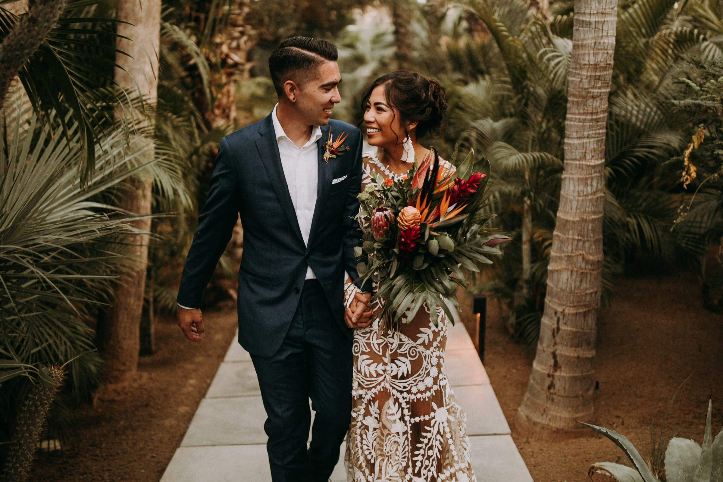 A wedding couple is walking down a pathway and is holding hands.