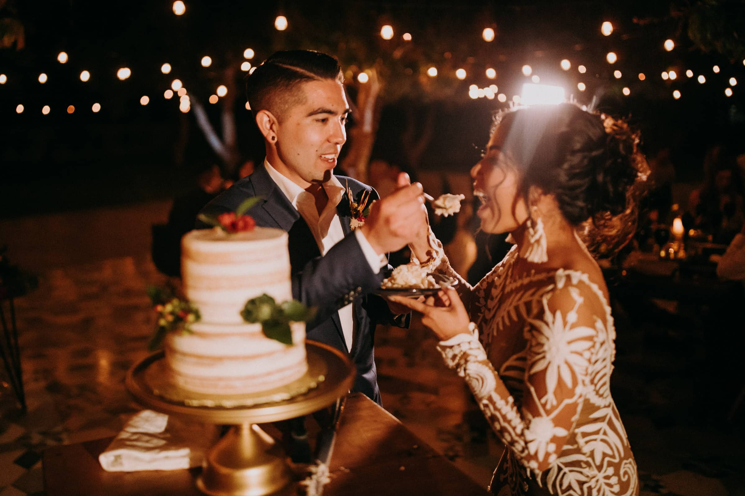 The wedding couple is tasting a spoon full of their wedding cake.