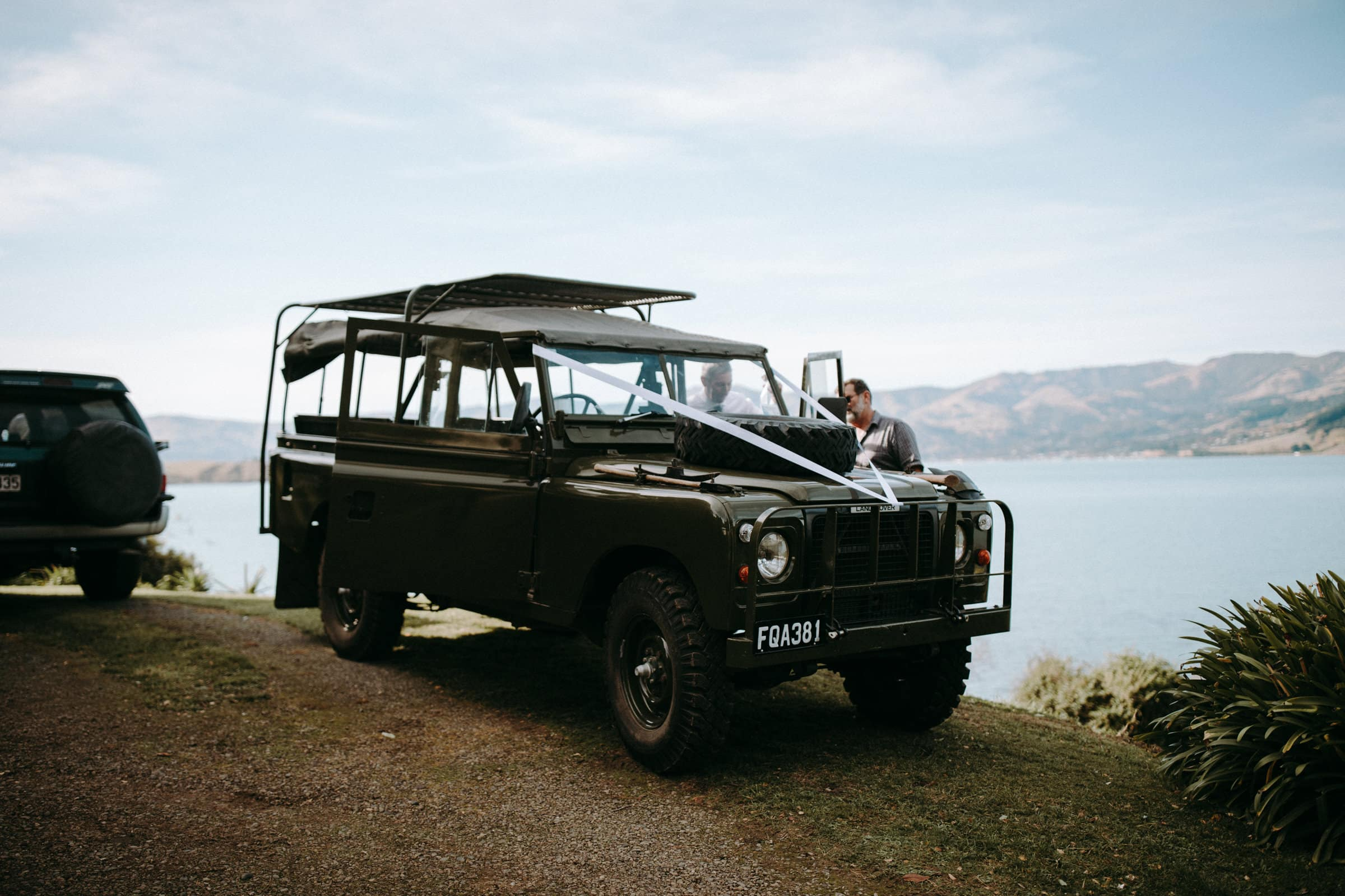 A Land Rover is decorated with white band and is standing next to a lake.