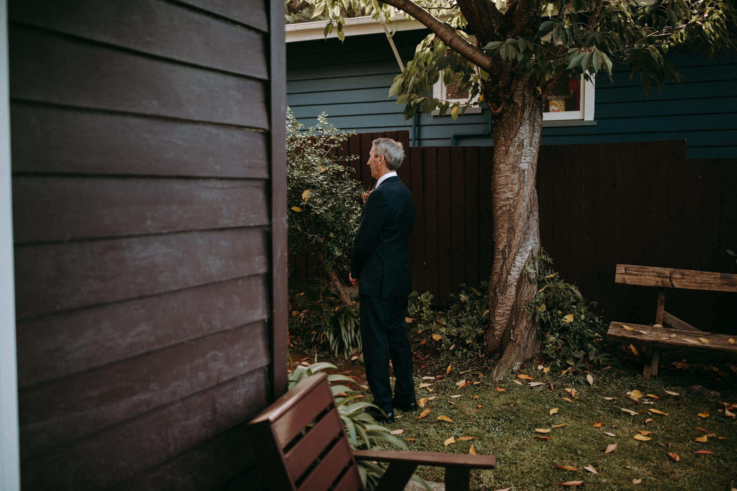 The brides father is waiting for his daughter in the garden.
