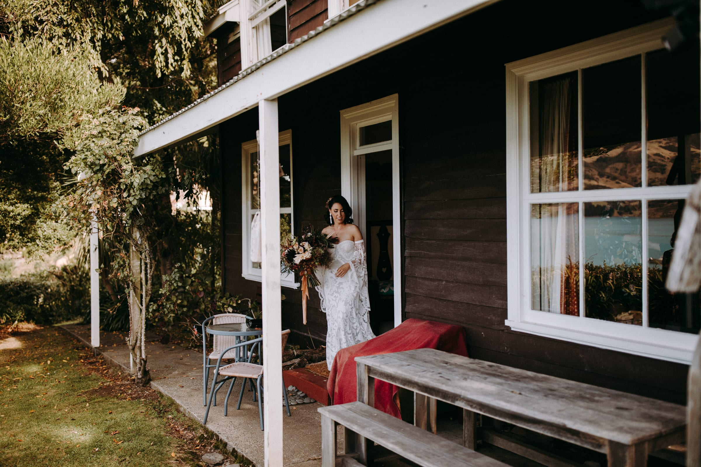 A bride is stepping out of the front door of a house and holding a flower bouquet.