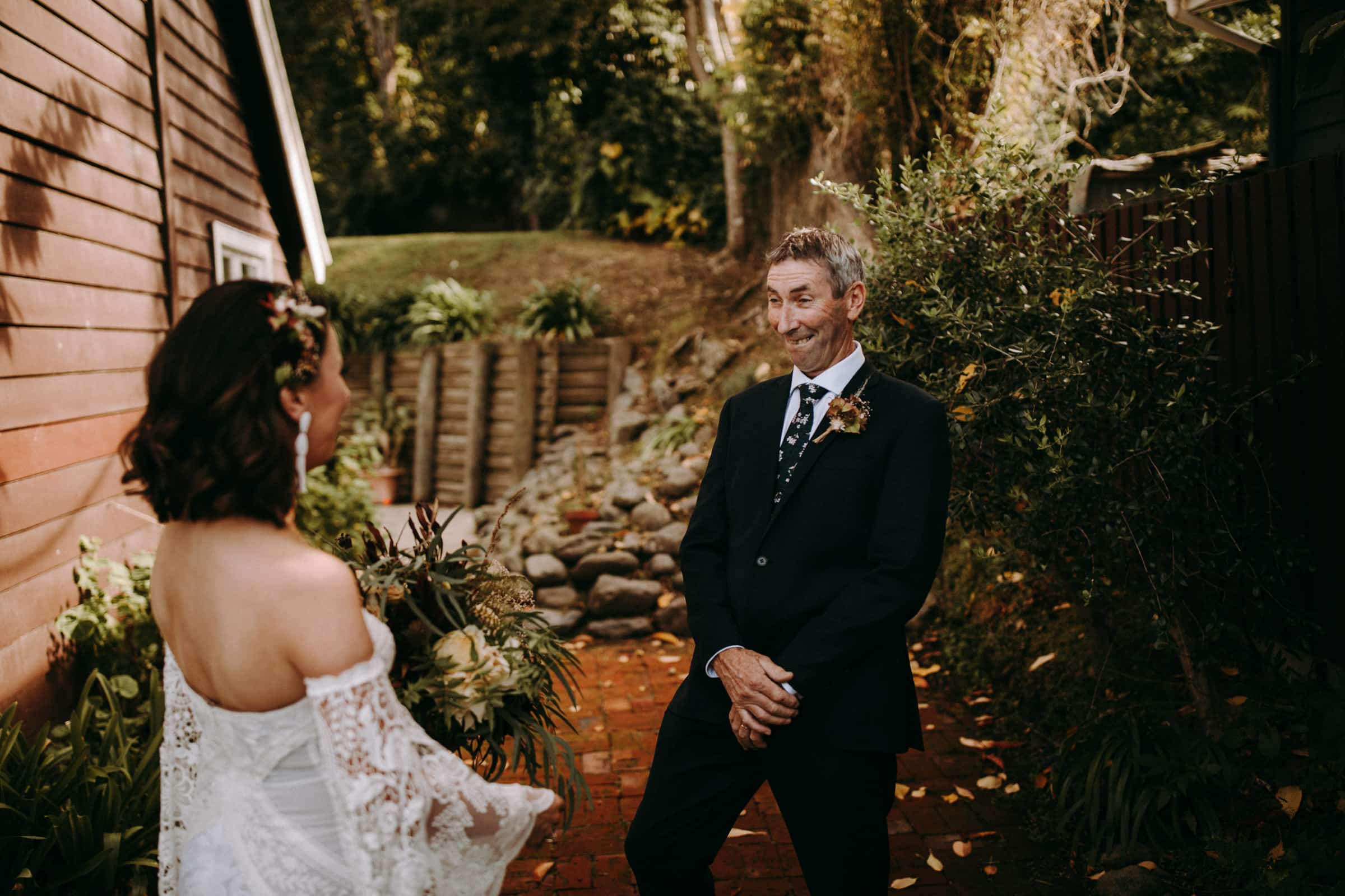 A bride and her father are having their first look and are standing in the garden.