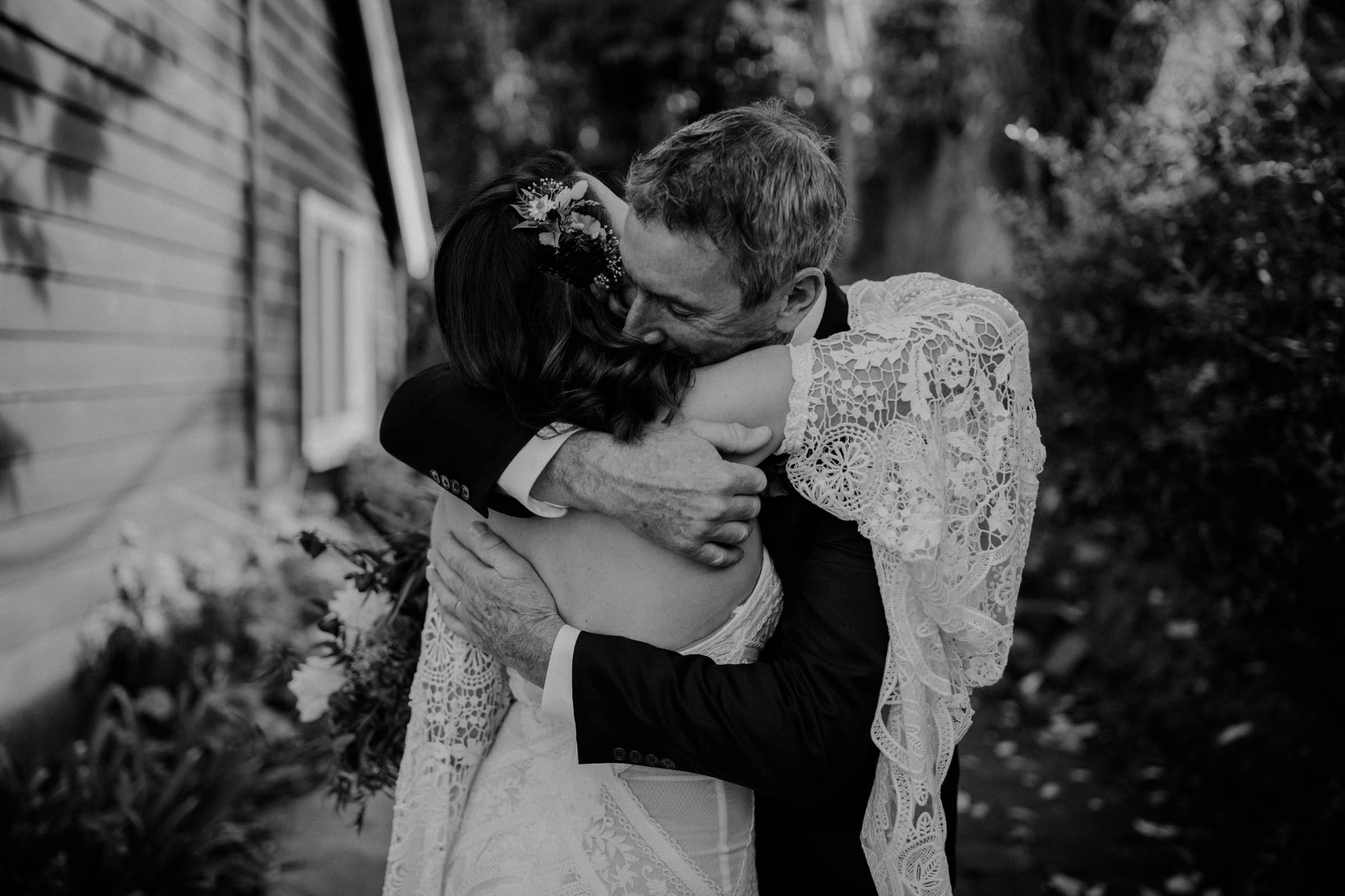A bride and her father are hugging each other.