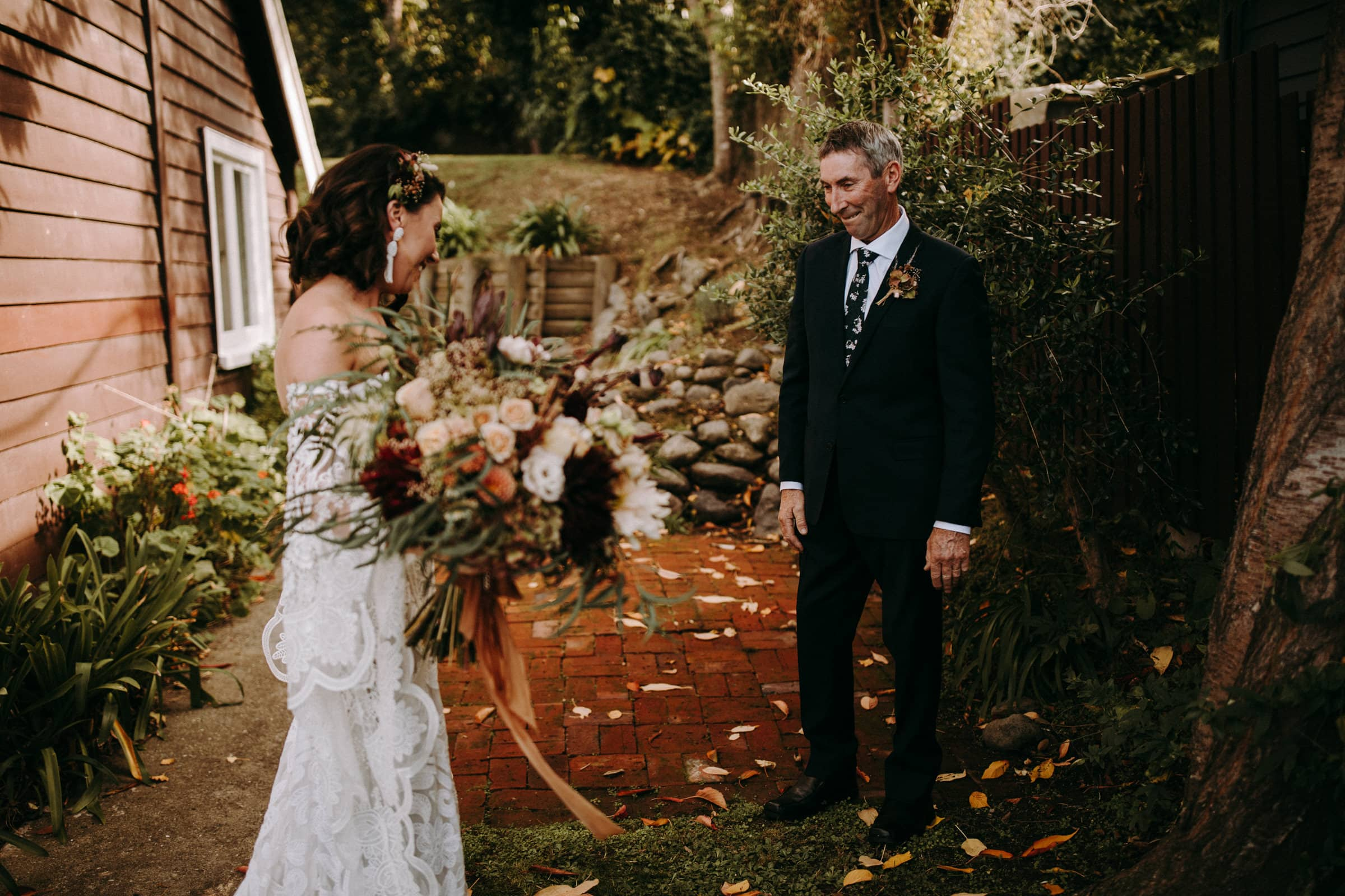 A bride and her father are looking at each other and are standing in the garden.