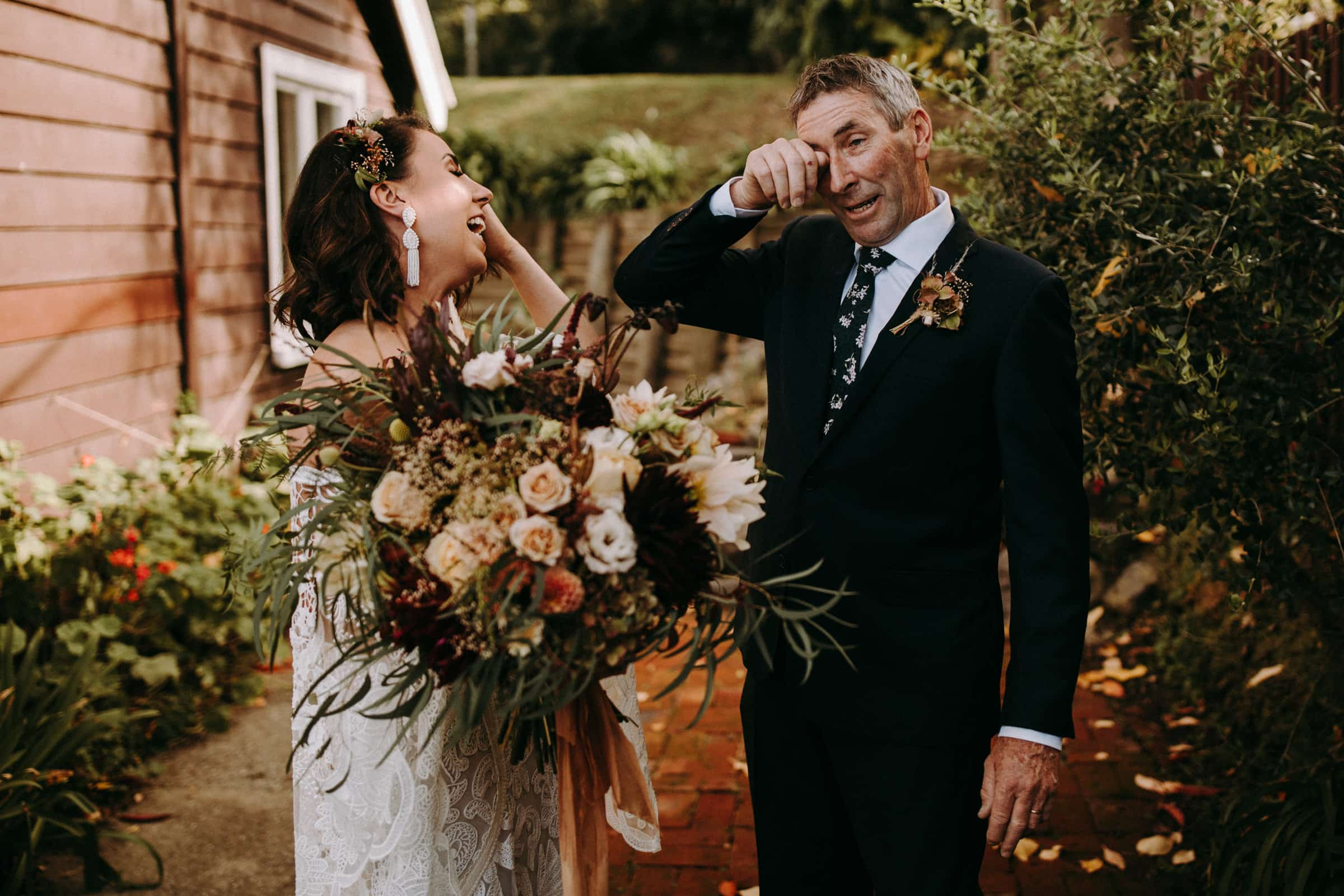 A bride and her father are laughing and crying and standing in the garden.