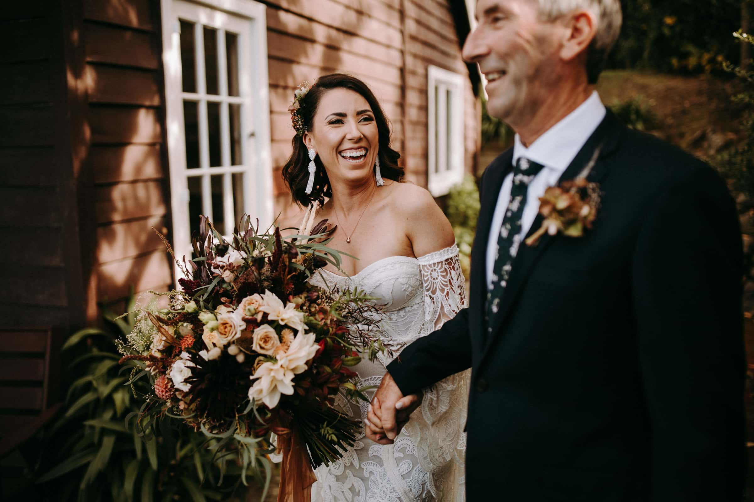 A bride and her father are holding hands and laughing.