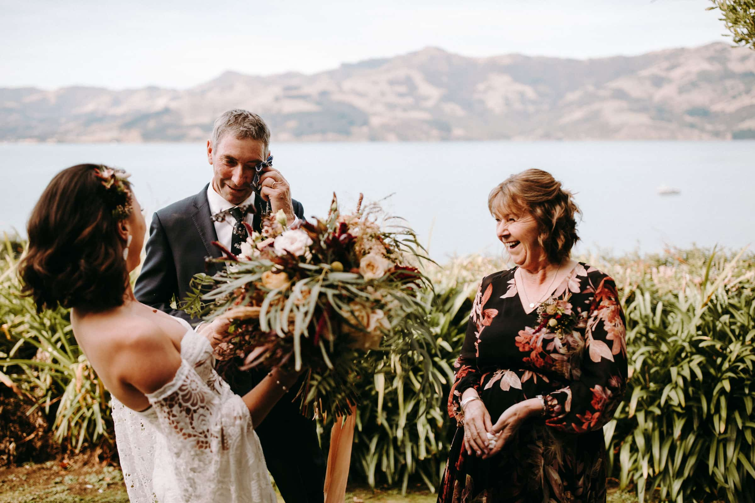 A bride and her parents are standing together and are smiling.