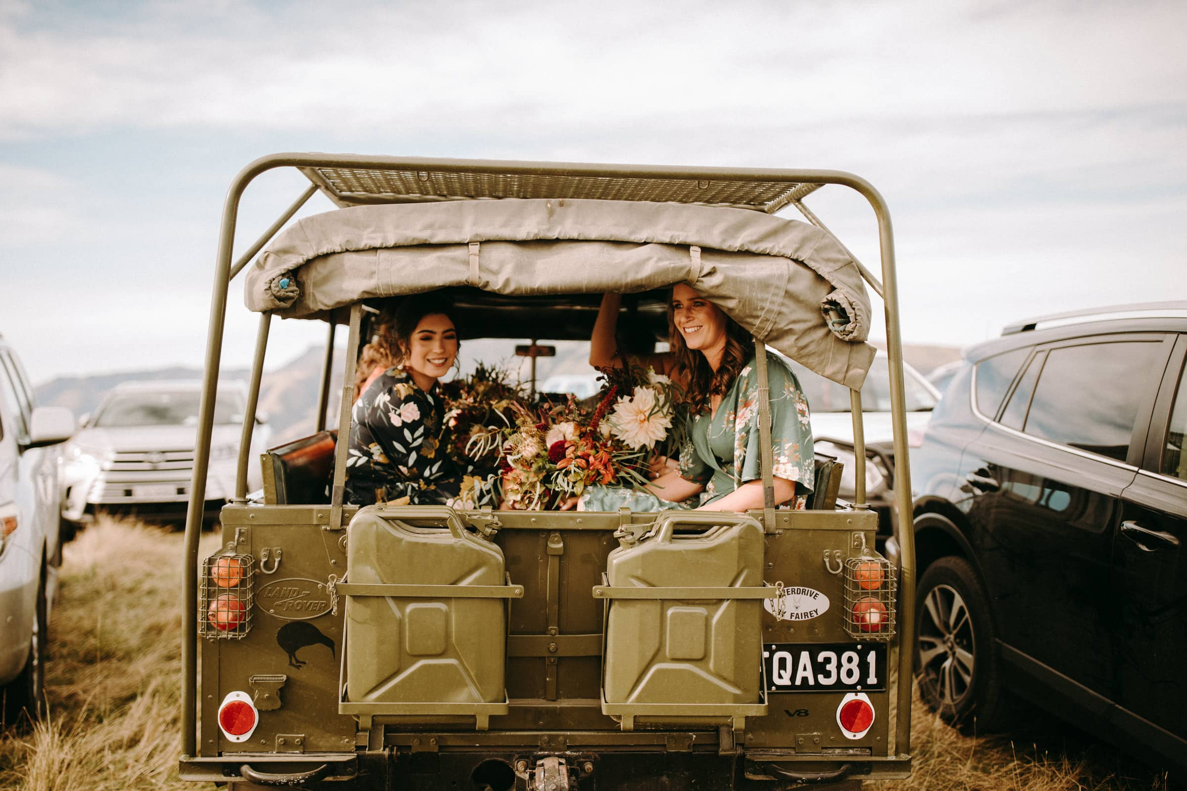 Wedding guests are sitting in a Land Rover.