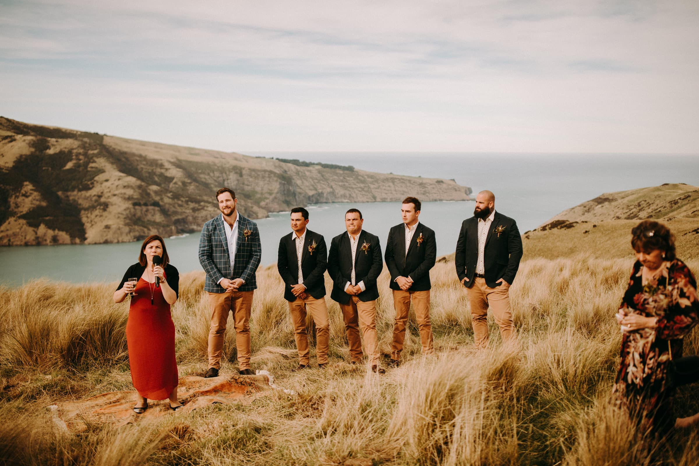 A groom, his groomsmen and other wedding guests are standing in a meadow.
