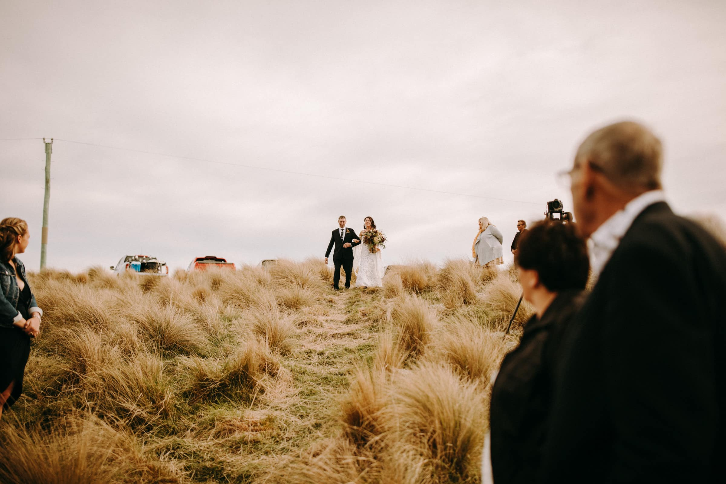 A bride and her father are walking down the aisle in a dry meadow.