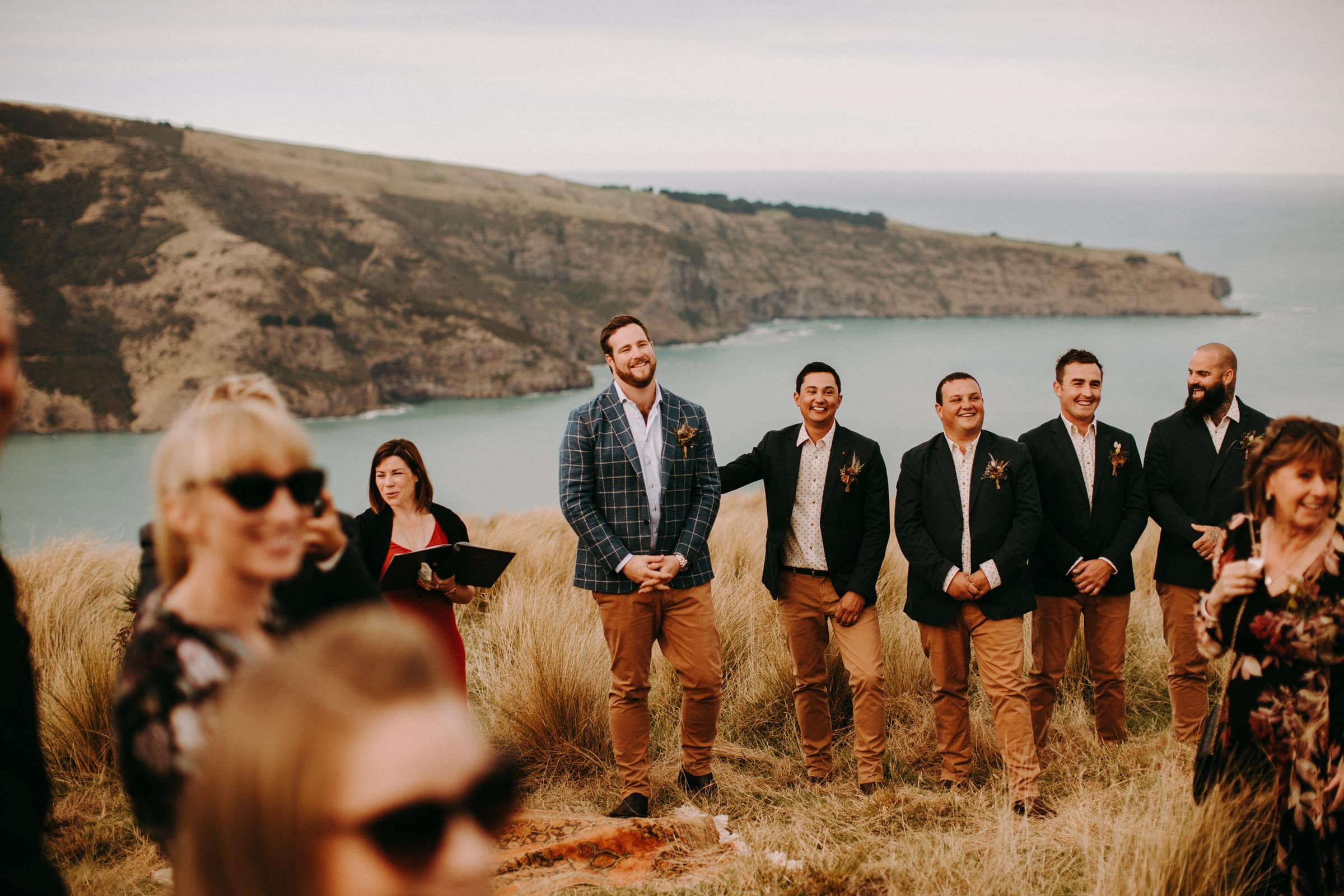 A groom, his groomsmen and other wedding guests are standing in a meadow and looking towards the bride.