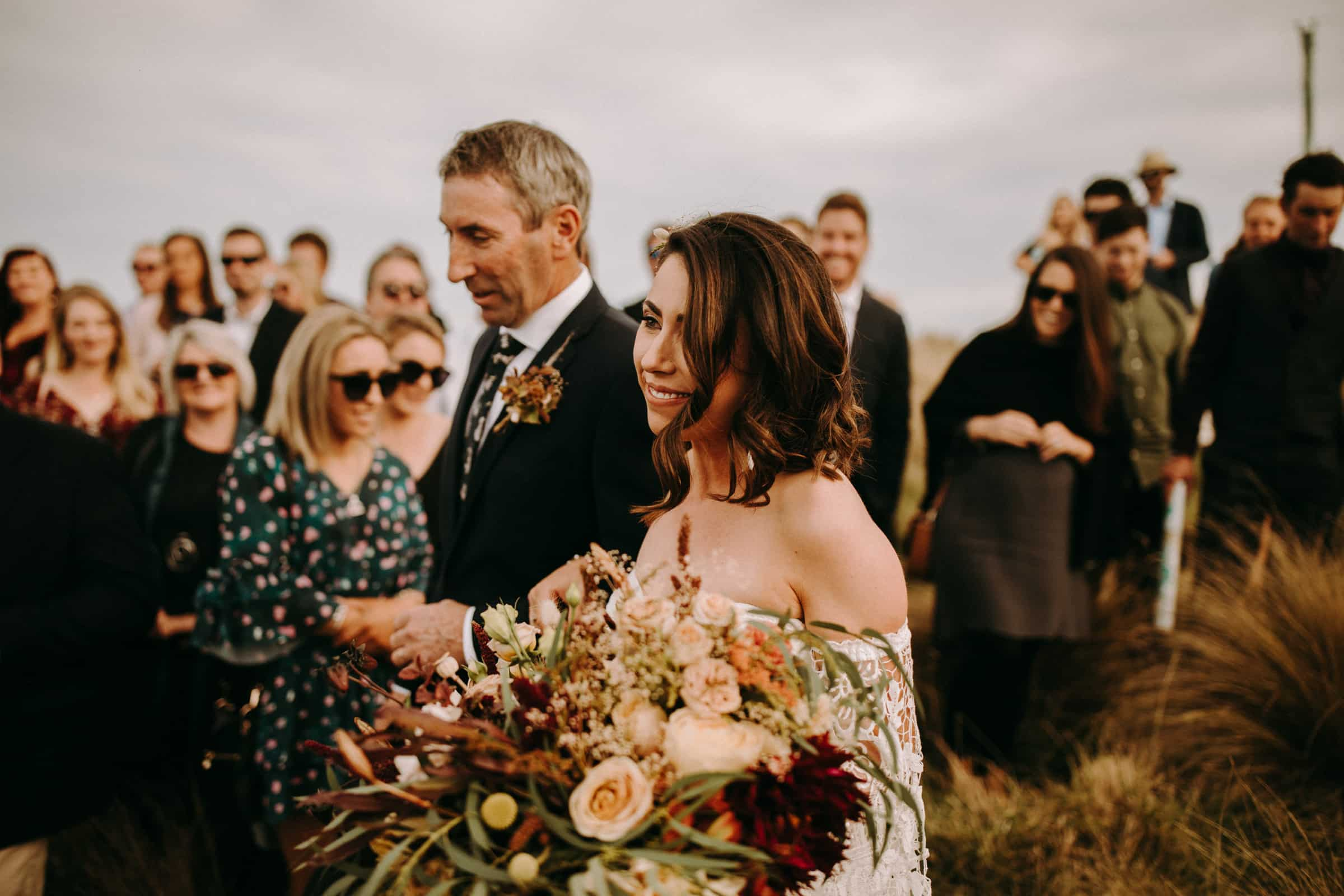 A bride and her father are walking down the aisle in a dry meadow and wedding guests are standing next to them.