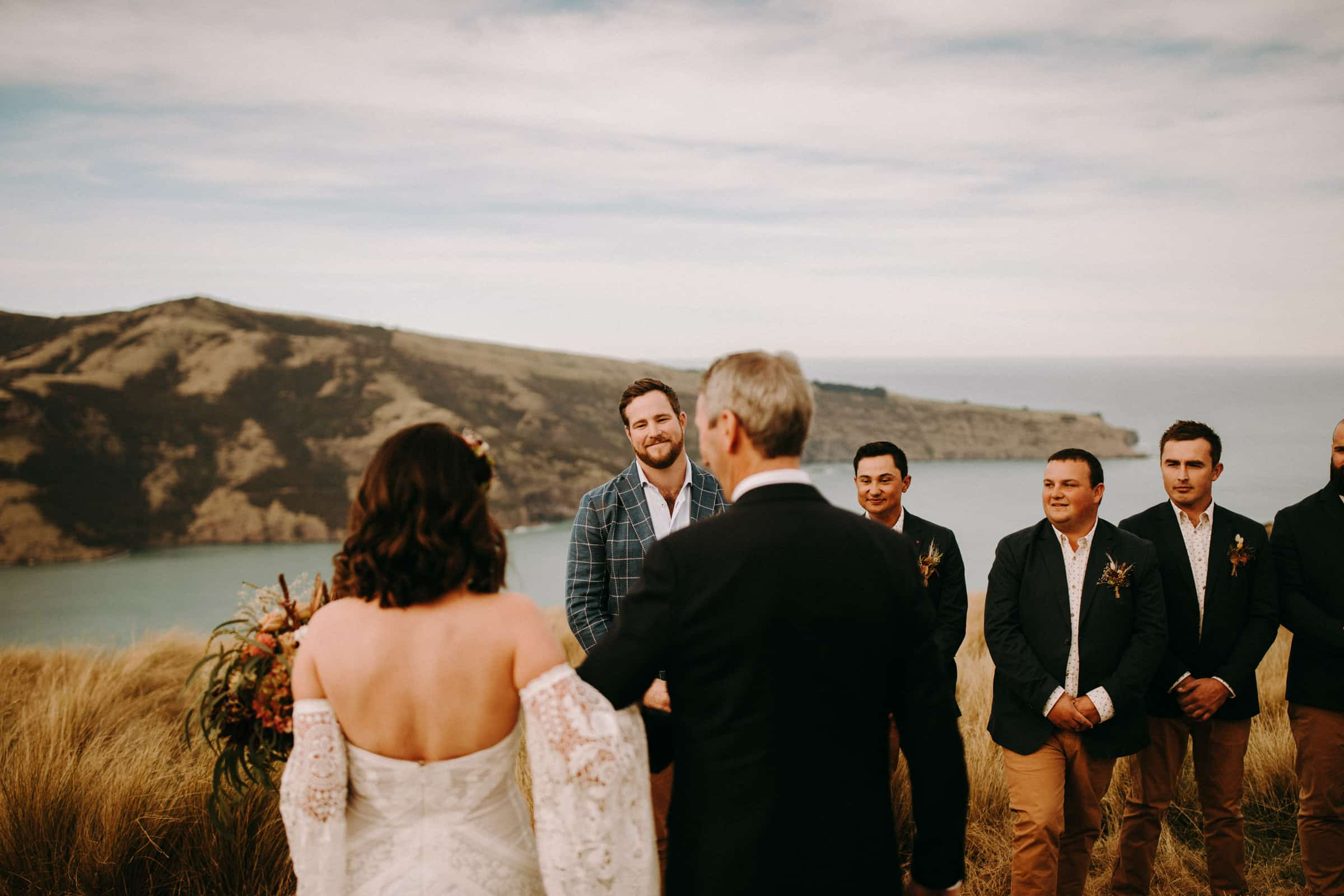 A bride and her father are standing in front of her groom and his groomsmen.