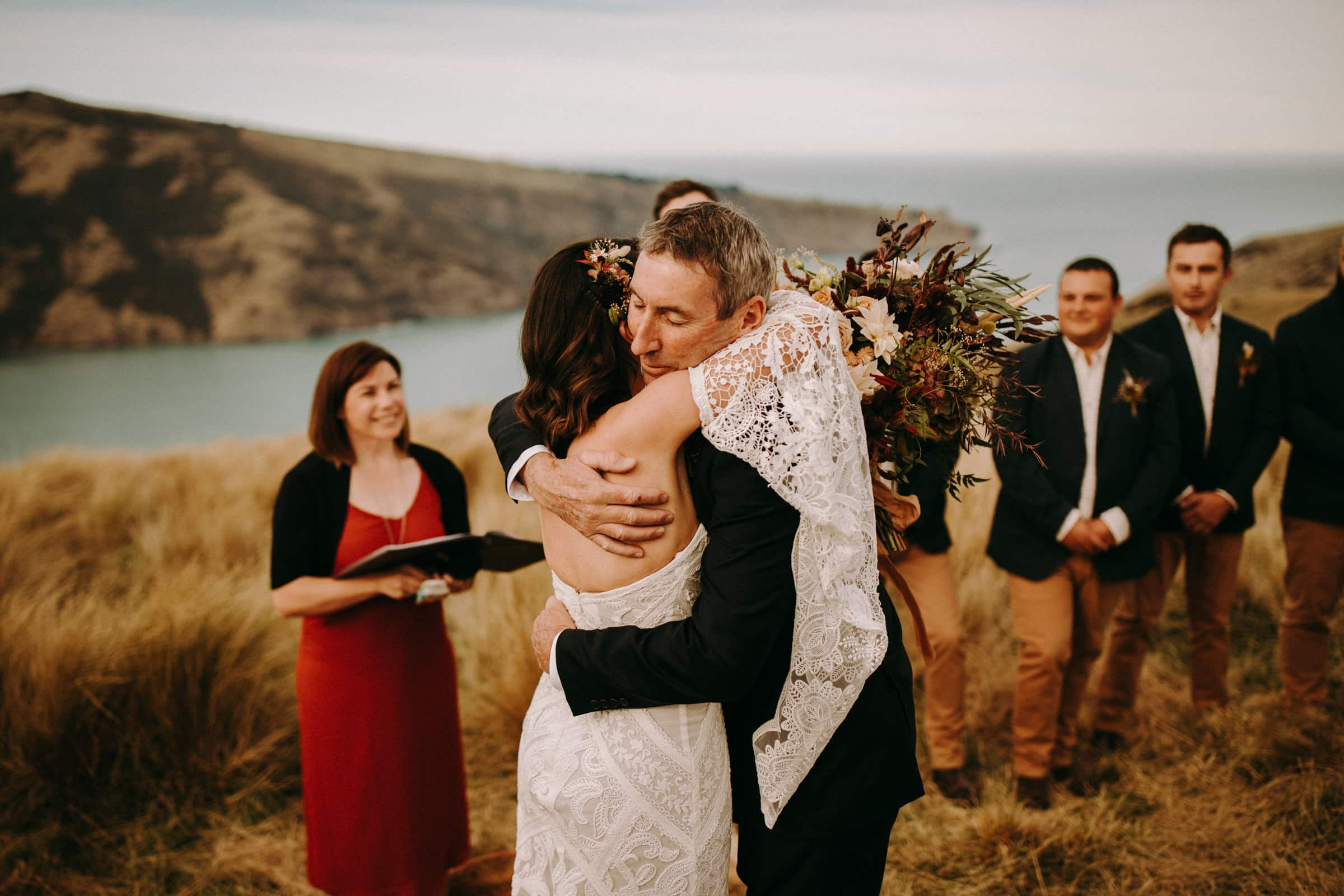 A bride is hugging her father in front of groomsmen.