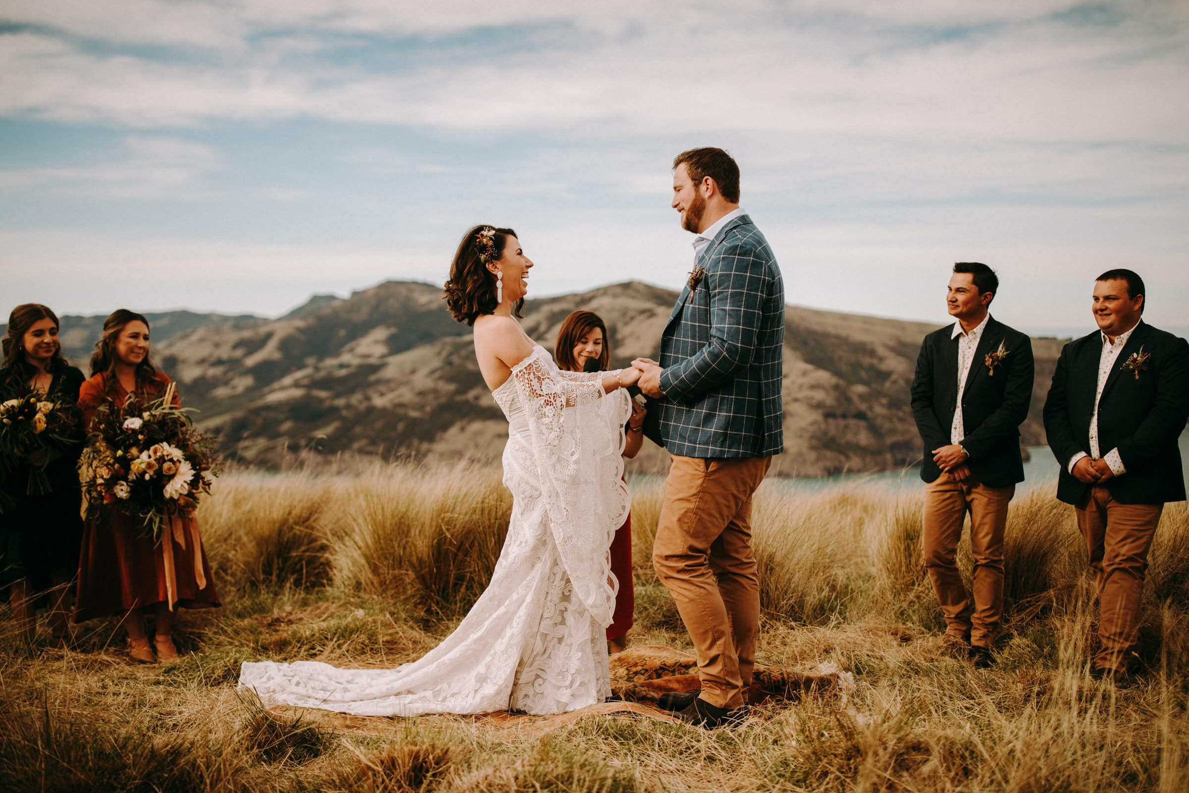 A bride and her groom are holding hands and standing in front of the ocean and mountains.