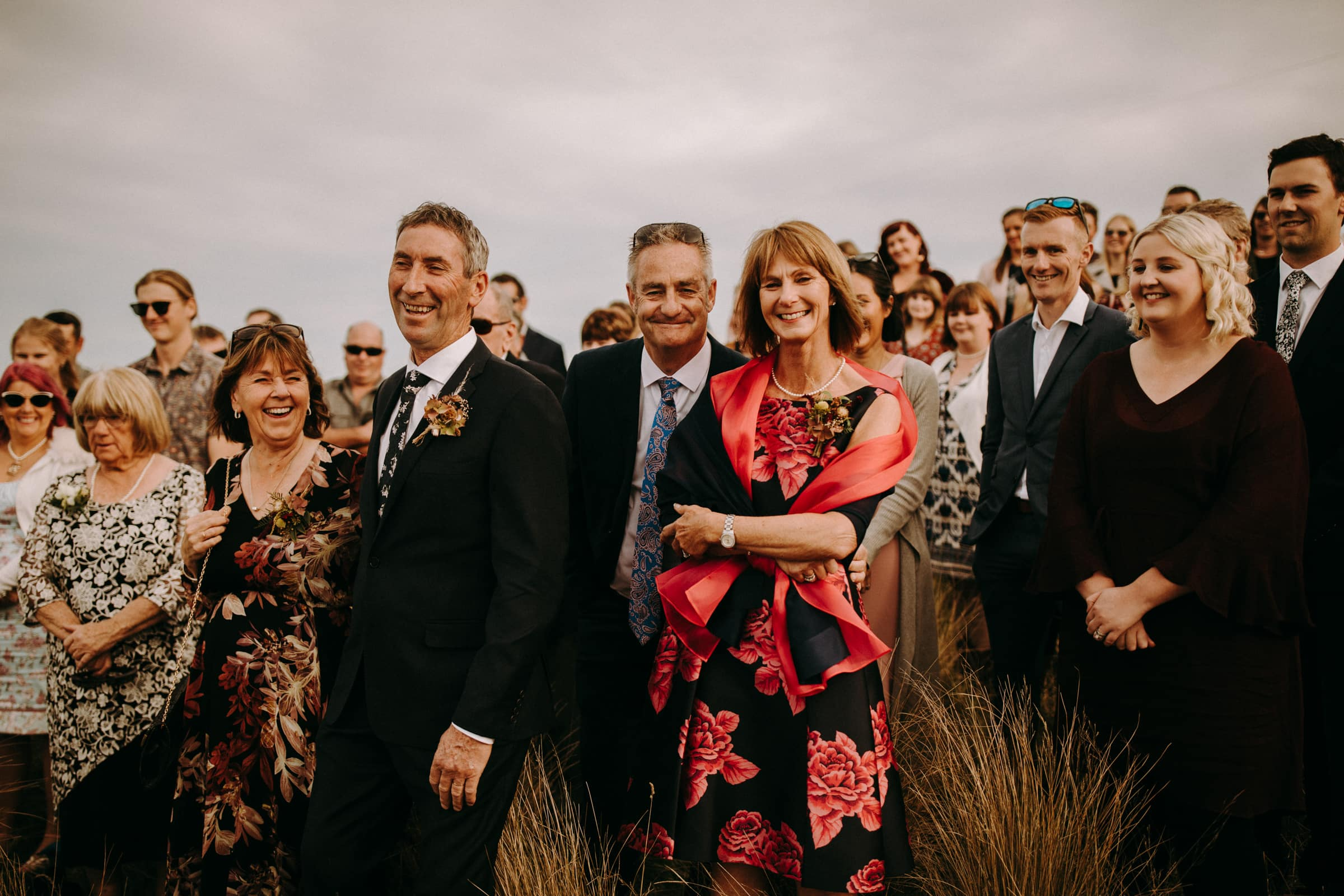 Wedding guests are standing in a meadow and are smiling.