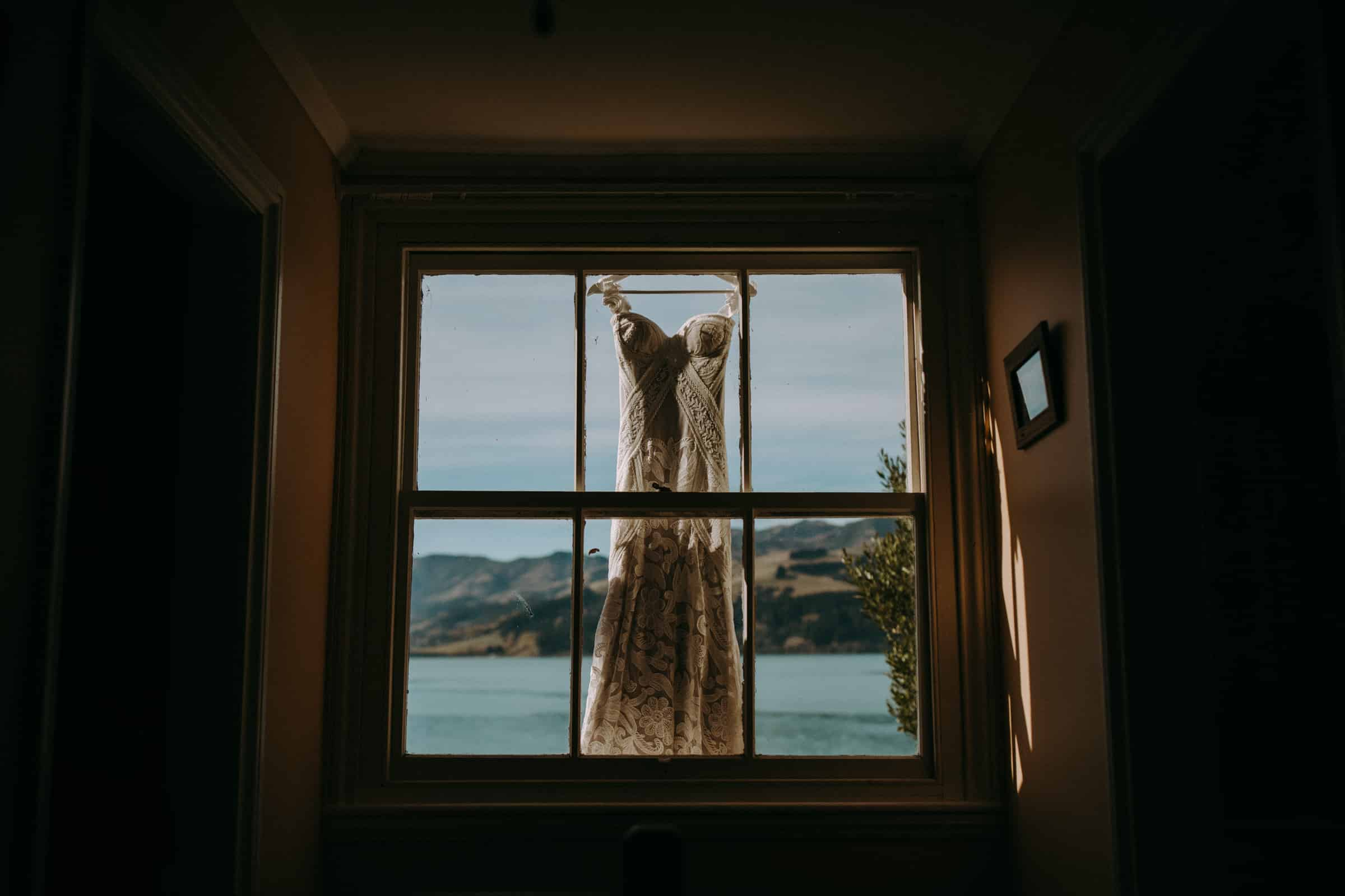 A wedding dress is hanging in front of a window.