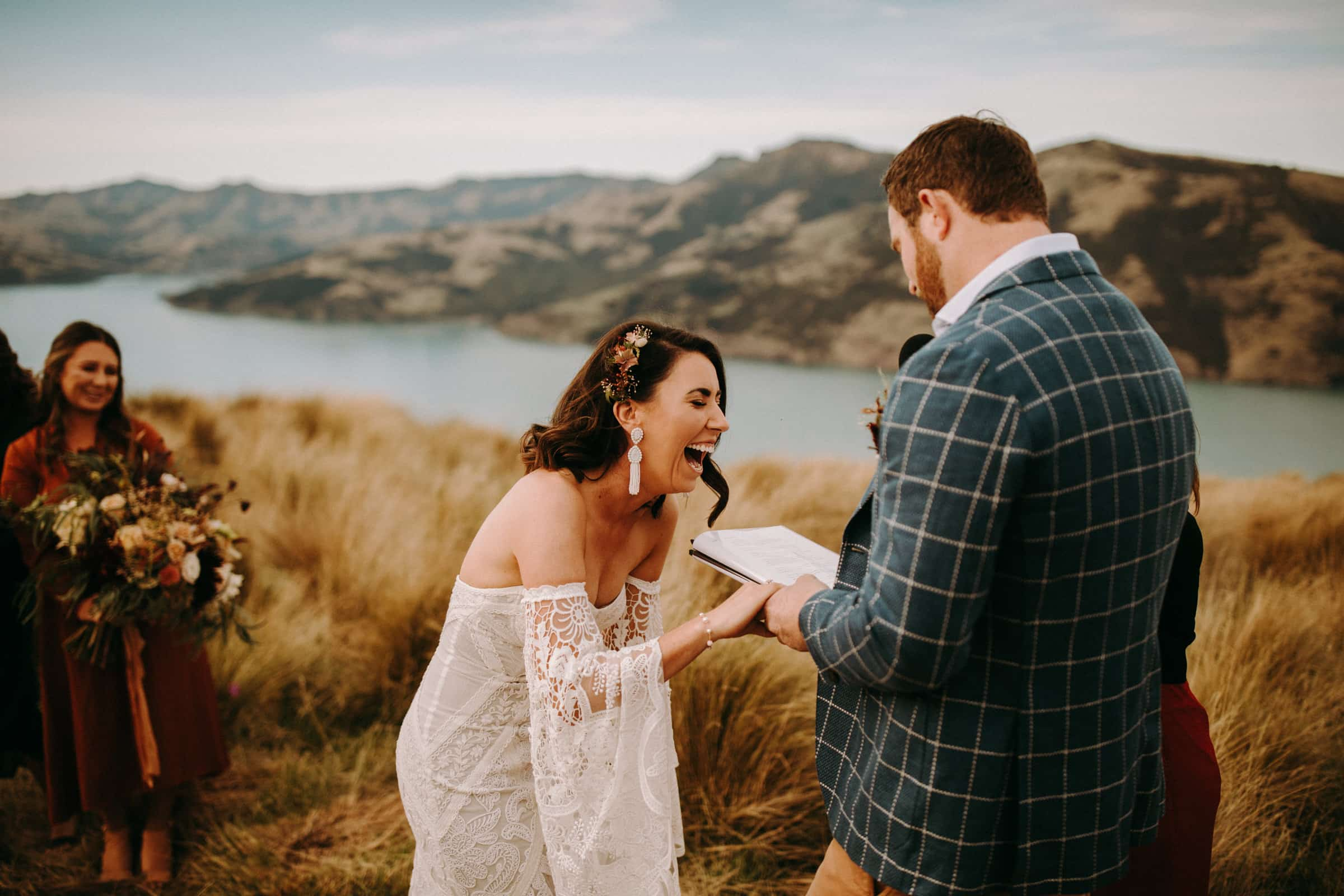 A bride and her groom are holding hands and are laughing at each other and the groom is reading out his vows.