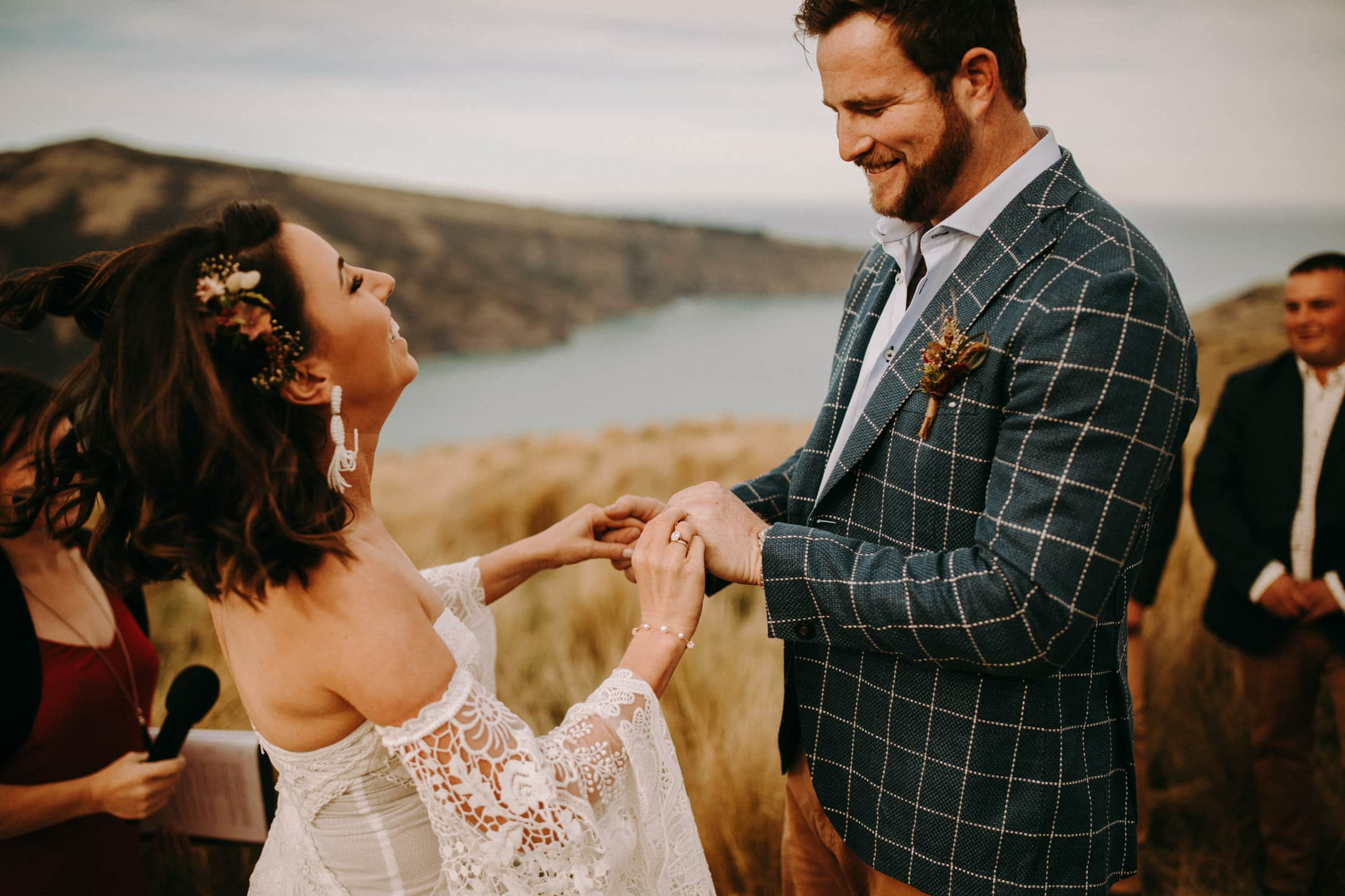 A wedding couple is exchanging wedding rings and both are smiling.
