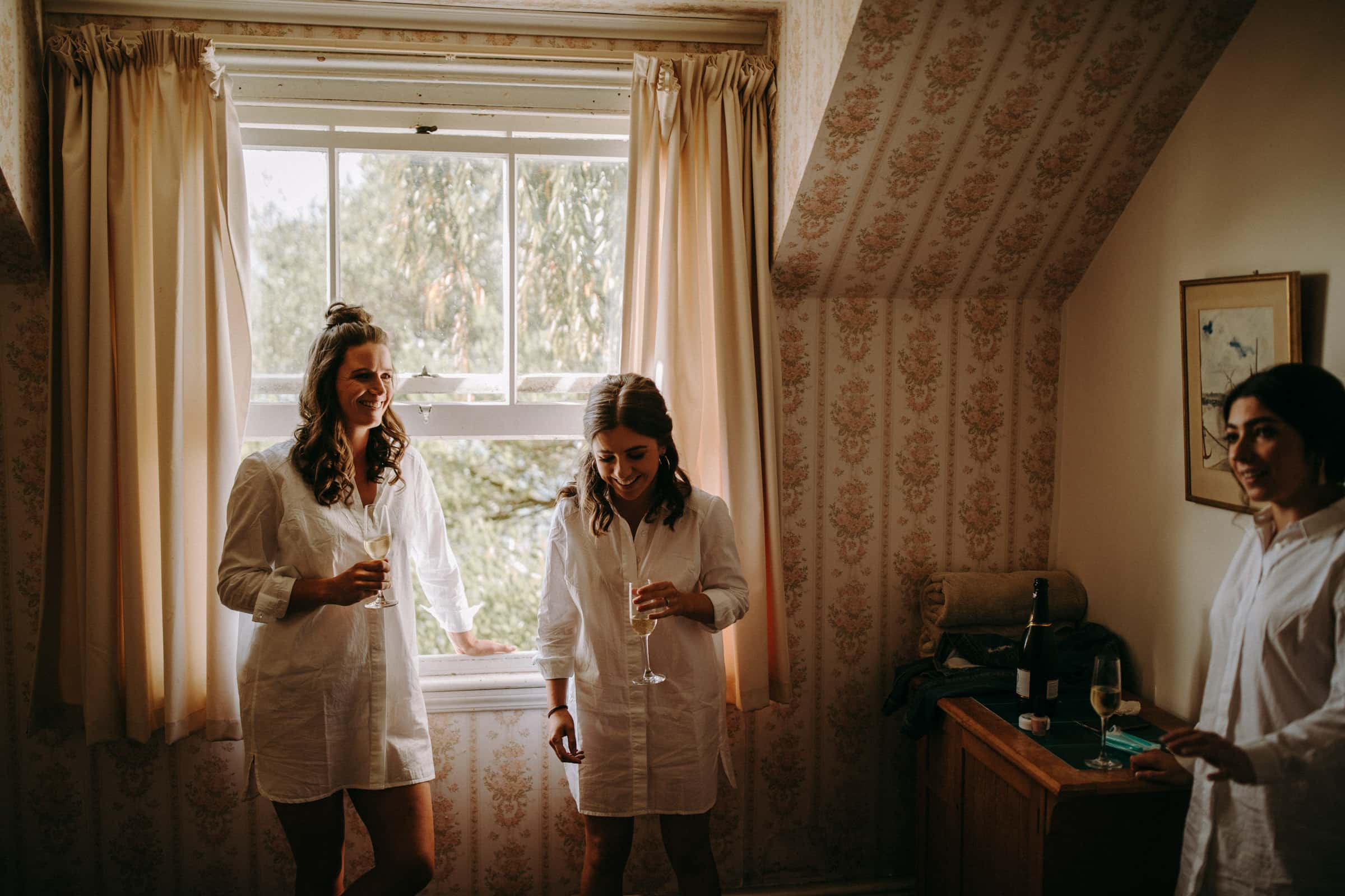 Bridesmaids are drinking champaign and laughing next to an open window.