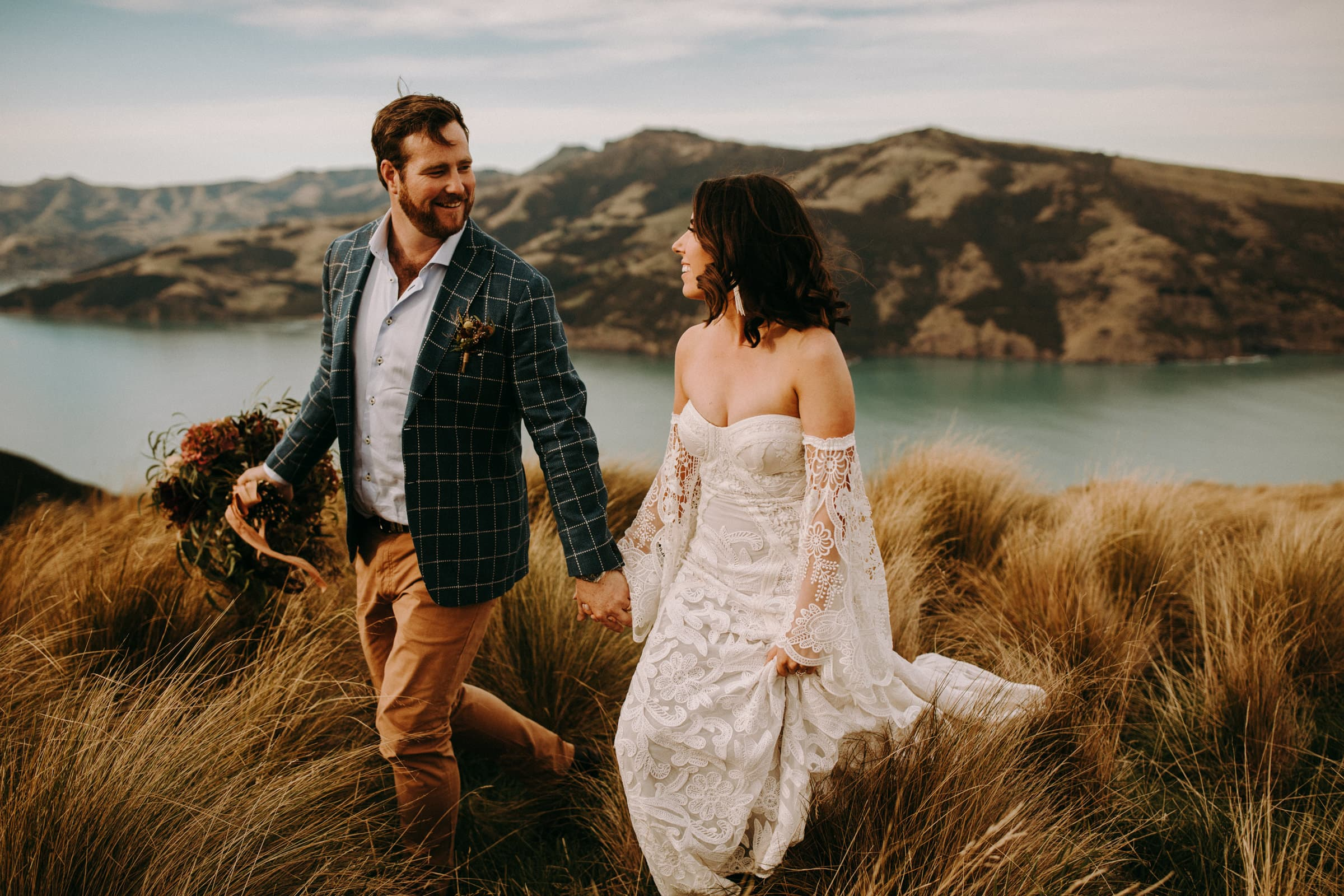 A wedding couple is walking in a meadow and is holding hands.