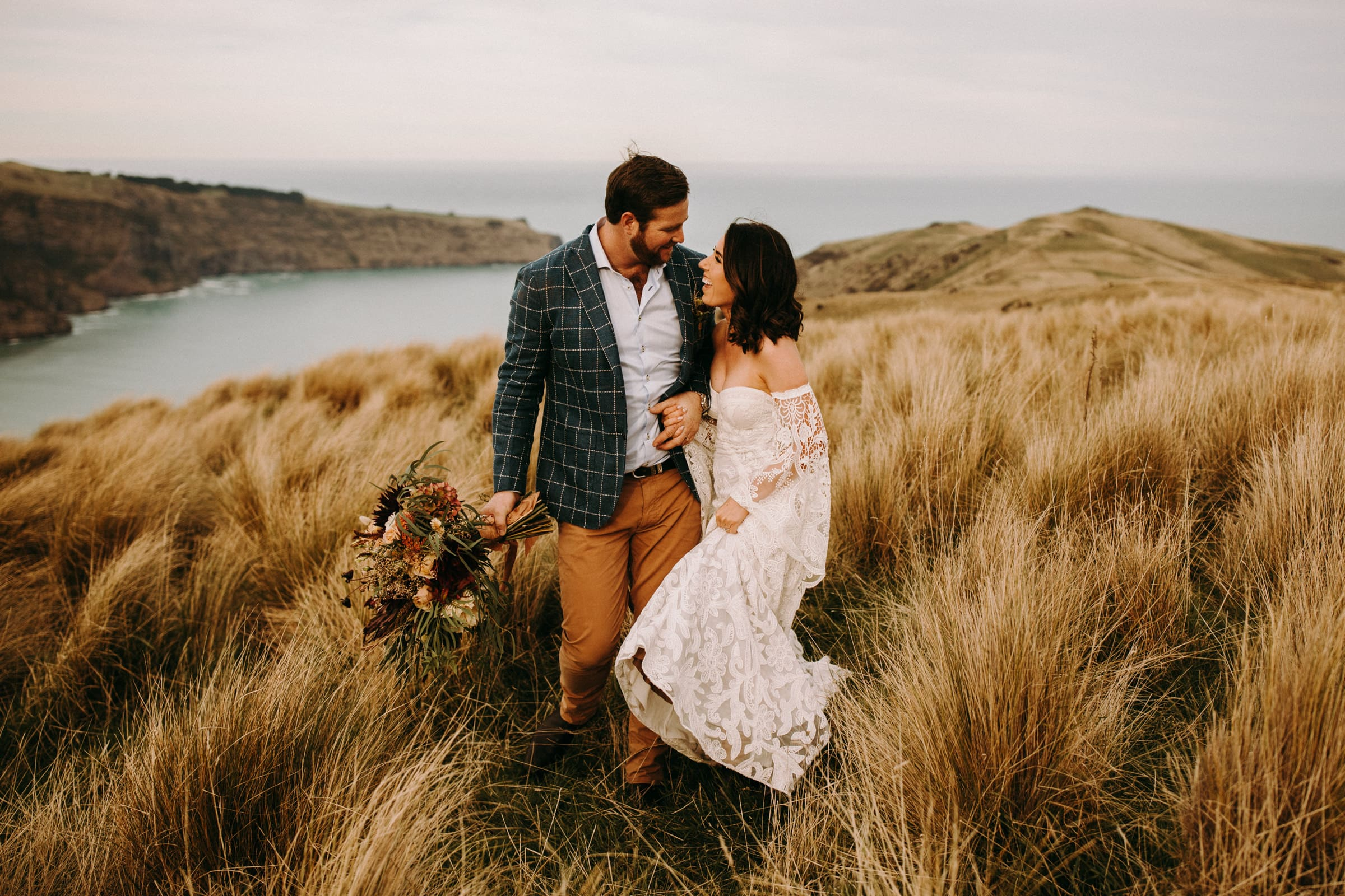 A wedding couple is standing in a meadow and is looking at each other.