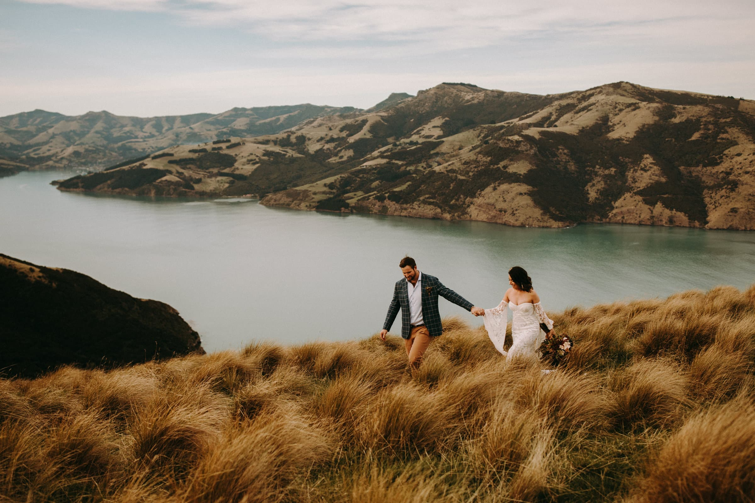 A wedding couple is walking through a meadow with a lake and mountains behind them.