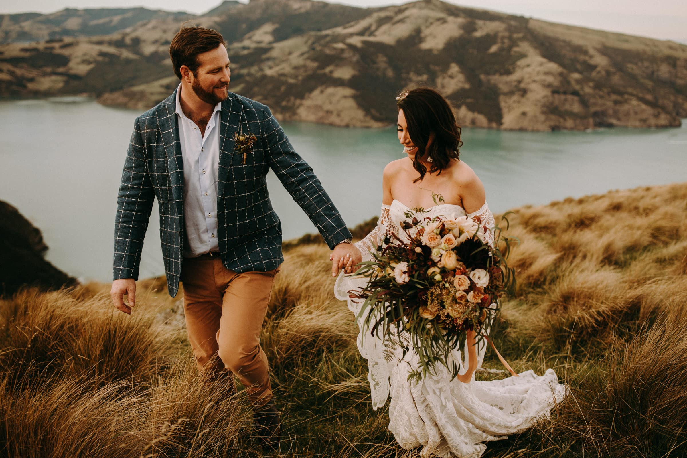 A wedding couple is looking at each other and walking in a meadow.
