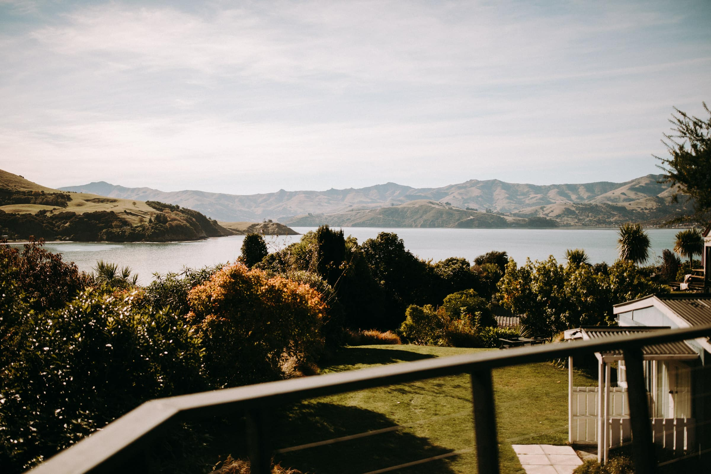 A New Zealand wedding destination features a balcony with a lawn, a lake and mountains.