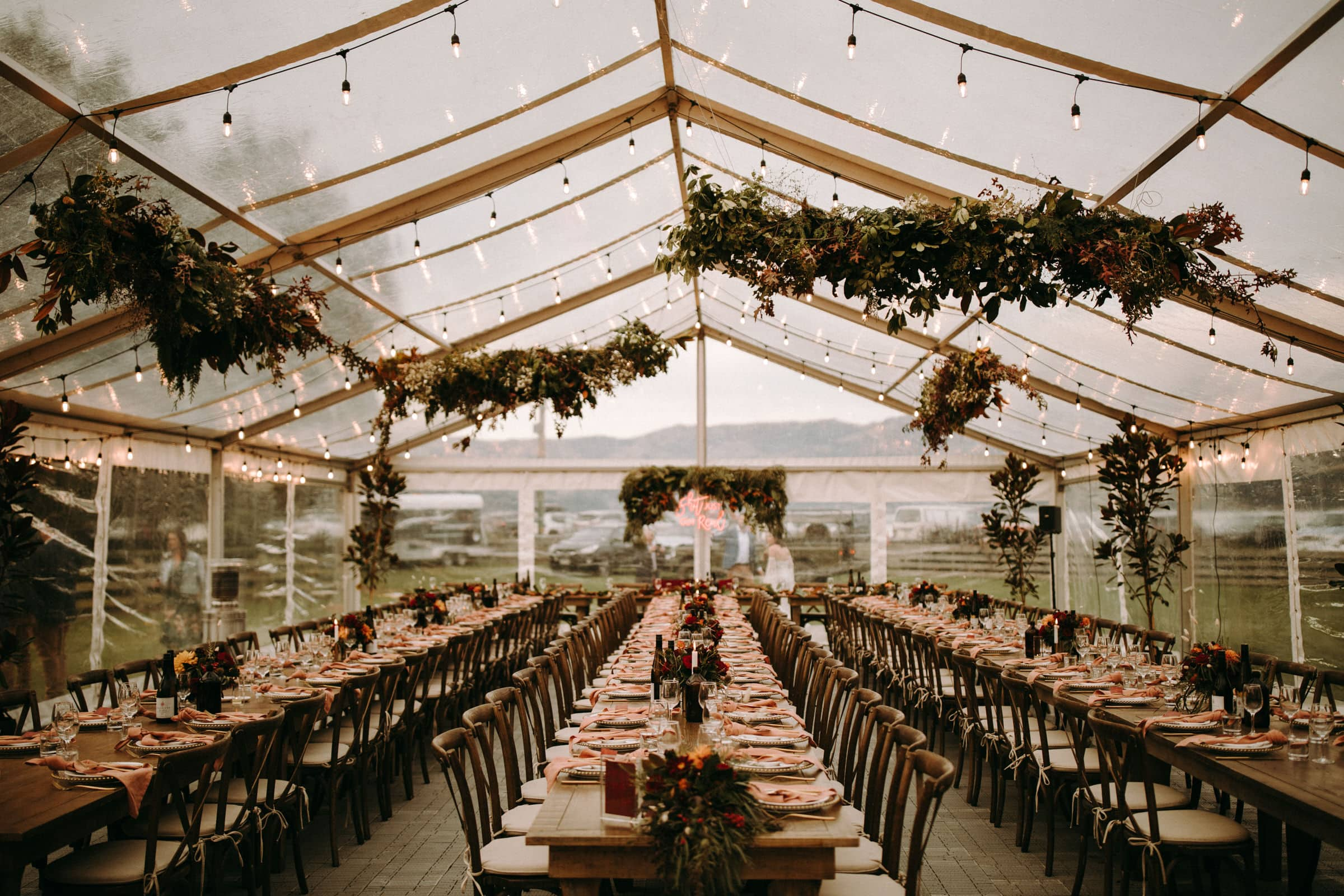 A big tent is decorated with light bulbs and branches and three rows of tables and chairs are located in it.